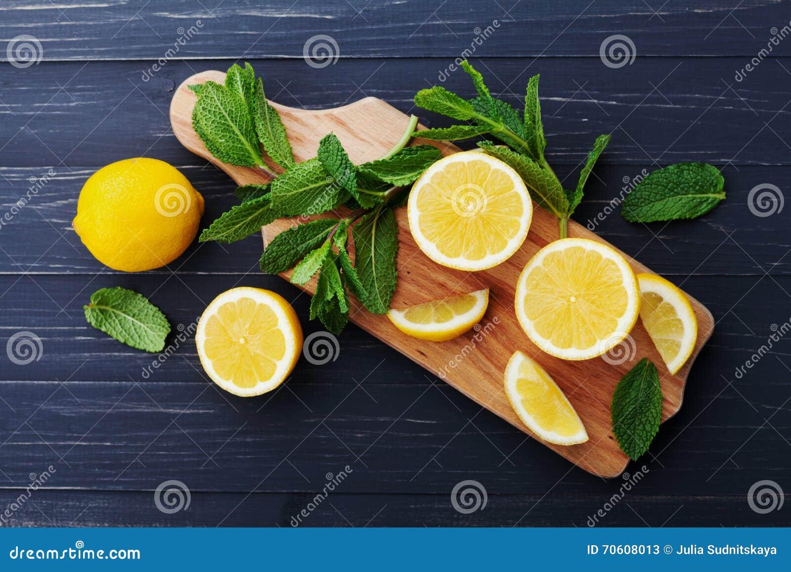 Τα φύλλα λεμονιών και μεντών εξυπηρέτησαν στον ξύλινο πίνακα κουζινών στο μαύρο αγροτικό πίνακα, το συστατικό για τα θερινά κοκτέ