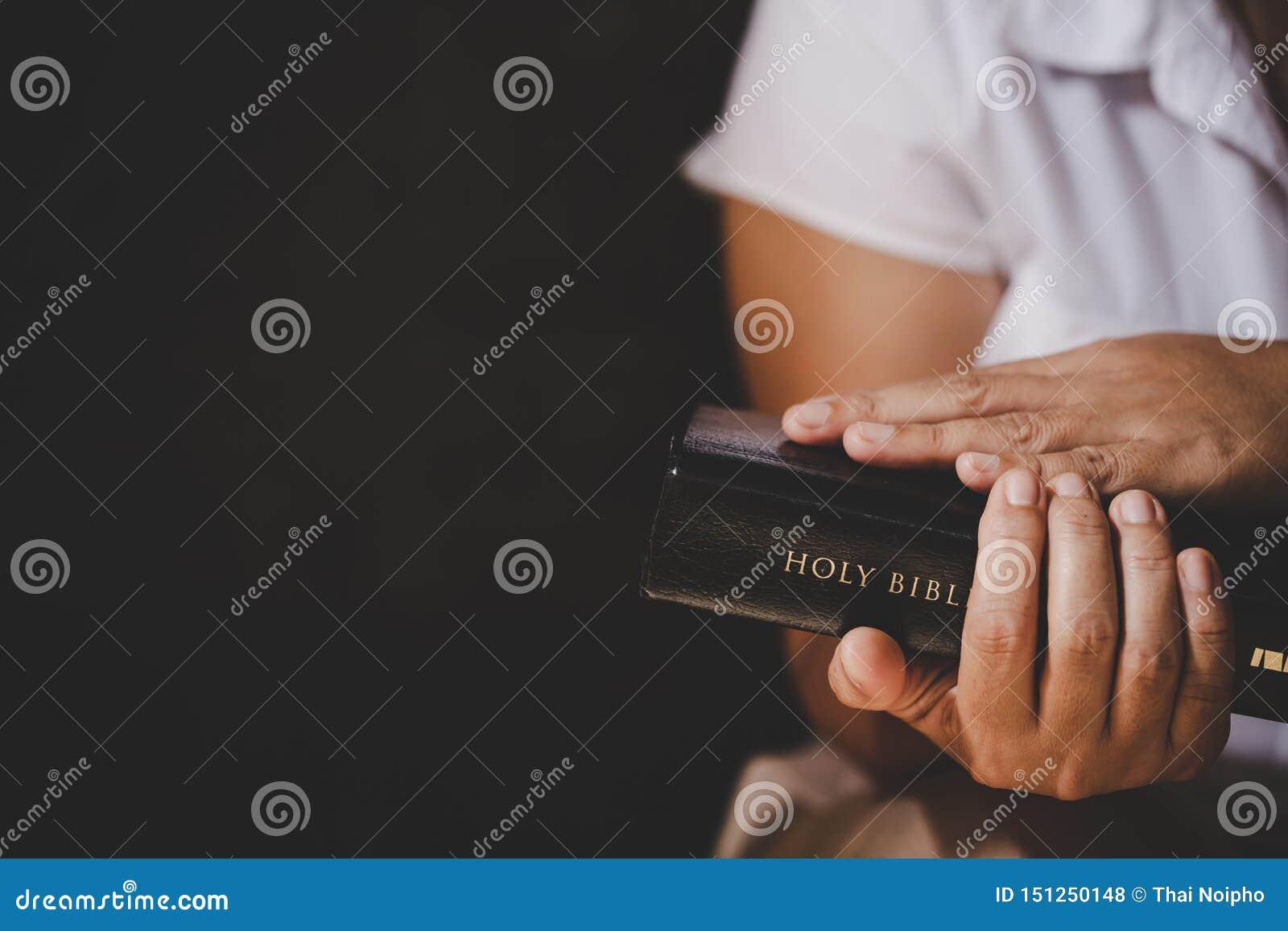 Τα χέρια δίπλωσαν στην προσευχή σε μια ιερή Βίβλο στην έννοια εκκλησιών για την πίστη