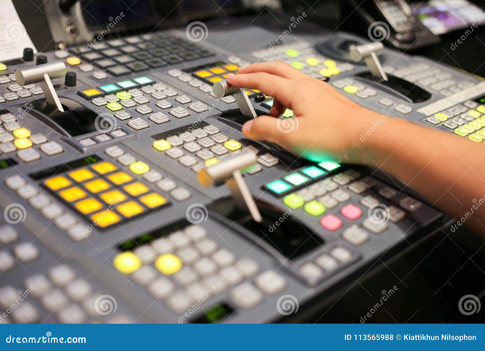 Τα χέρια διαλύουν επάνω Switcher των κουμπιών στο τηλεοπτικό κανάλι στούντιο, Audi