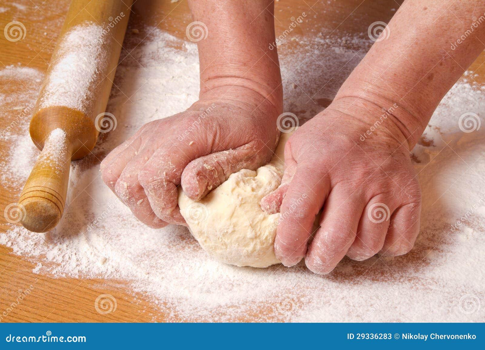 Τα χέρια του αρτοποιού ζυμώνουν μια ζύμη κομματιού
