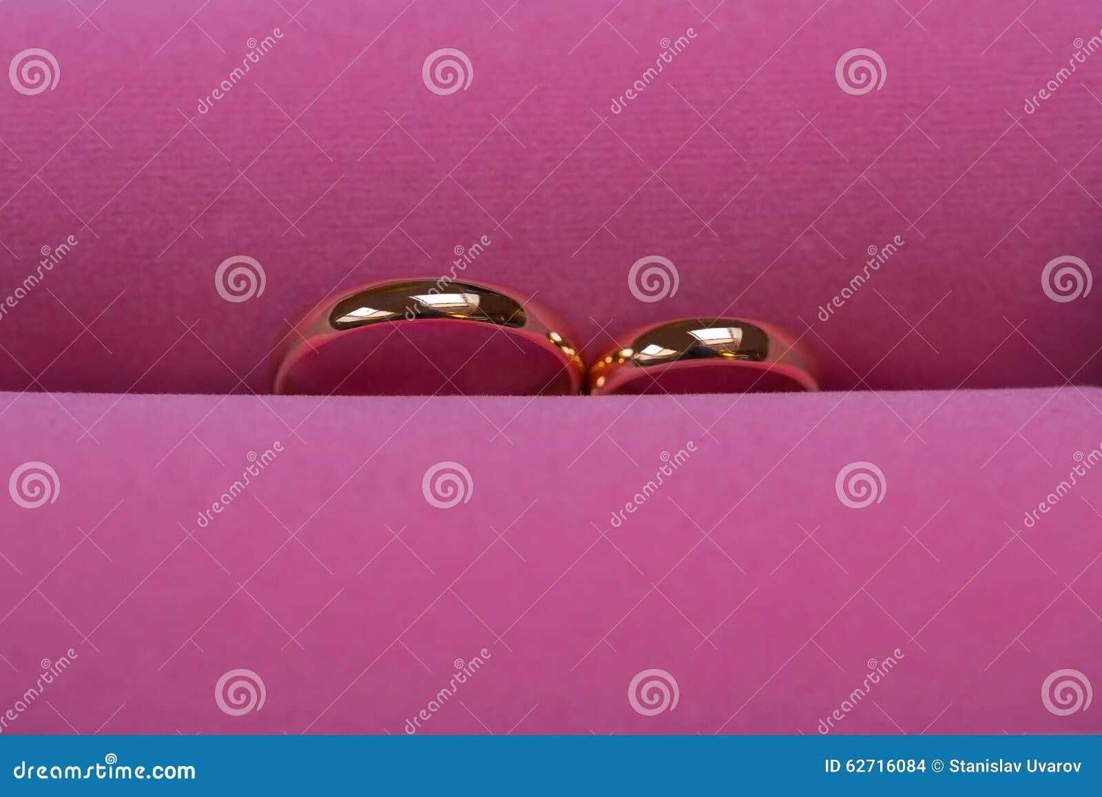 Τα χρυσά γαμήλια δαχτυλίδια στο ρόδινο υπόβαθρο, κλείνουν επάνω