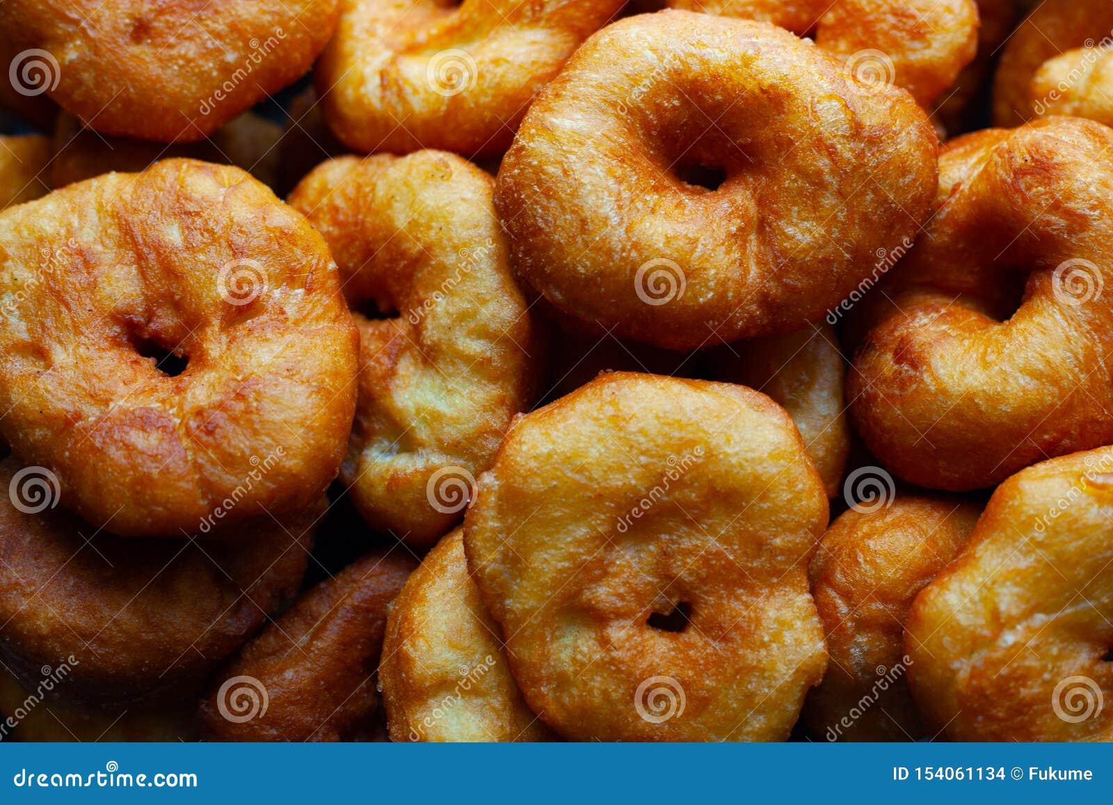 Τα χρυσά γλυκά donuts τηγάνισαν στο ηλιέλαιο, επιβλαβές γρήγορο μαγείρεμα τροφίμων οδών