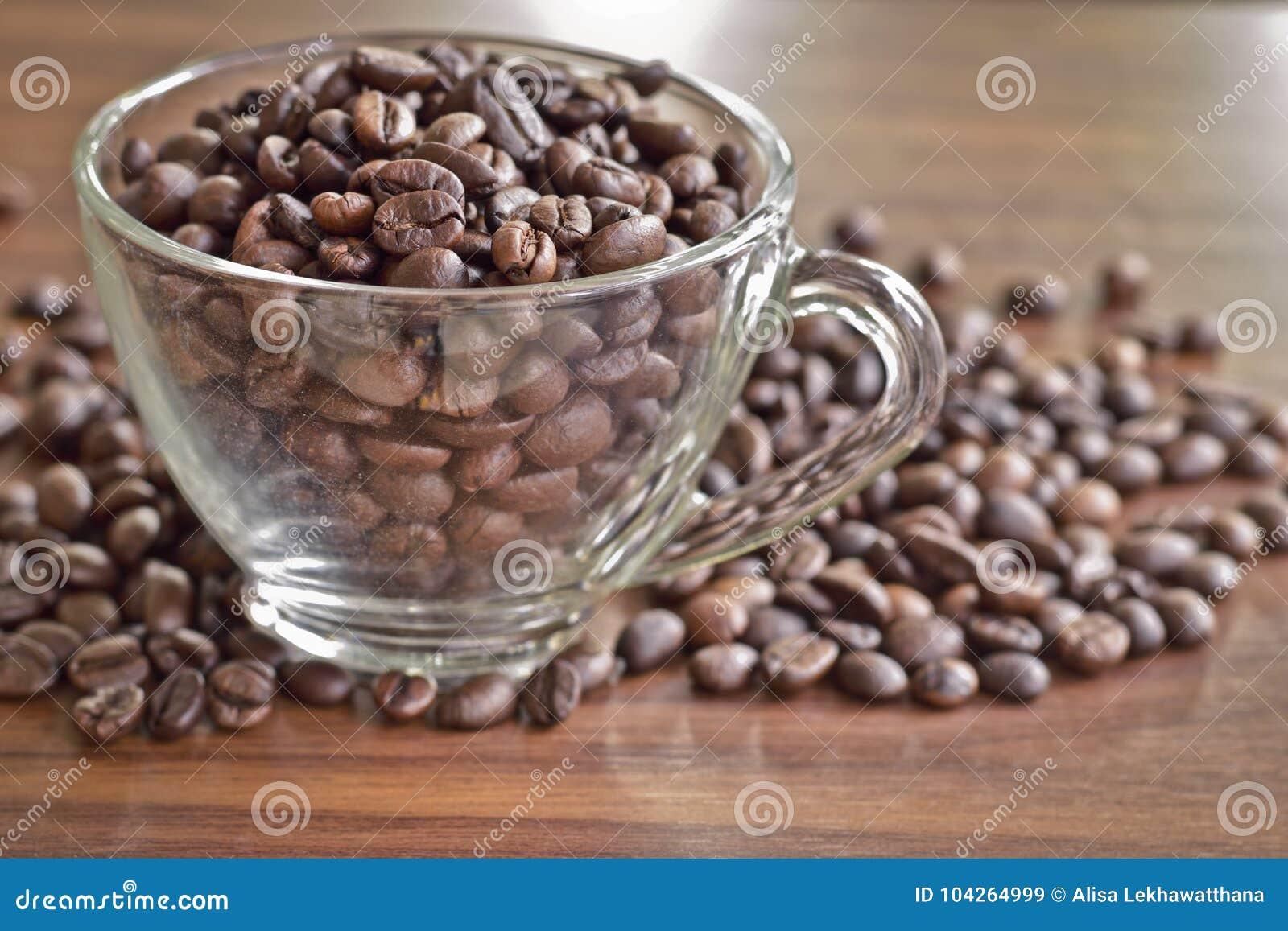 Τα ψημένα φασόλια καφέ σε ένα φλυτζάνι και έναν σωρό του καφέ βάζουν στο ξύλινο τ