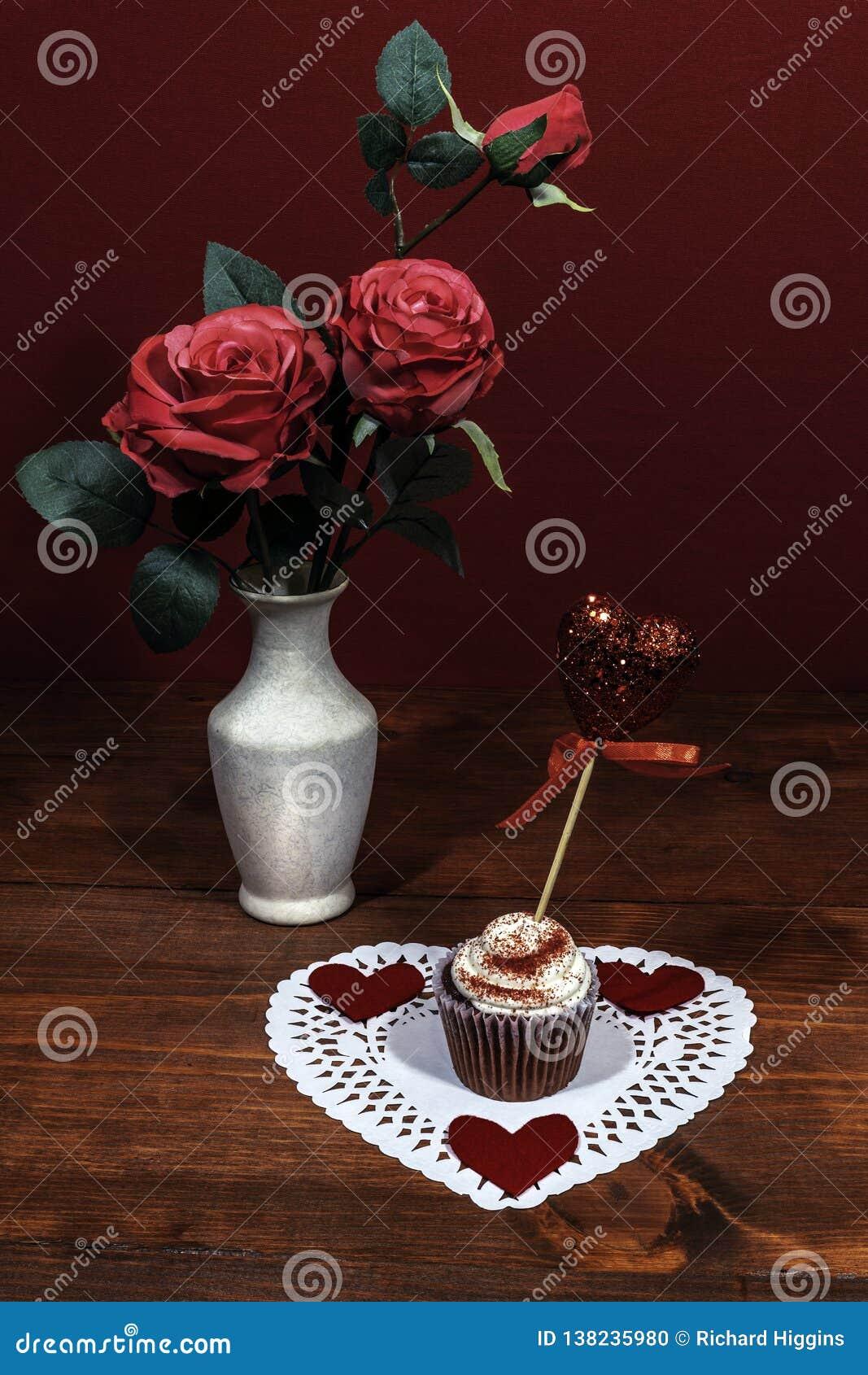 Τα όμορφα ρόδινα τριαντάφυλλα σε ένα βάζο, καρδιά το άσπρο dollie με ένα διακοσμημένο κέικ φλυτζανιών σε το με μια καρδιά σε μια