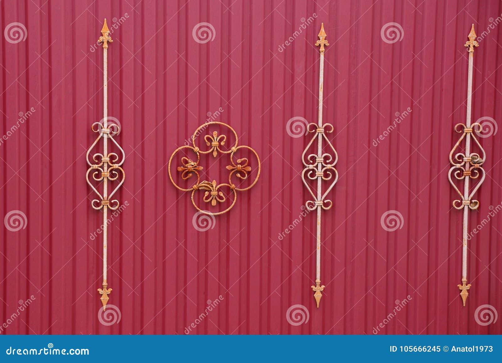 Τεμάχιο ενός κόκκινου φράκτη με τους σφυρηλατημένους φραγμούς και ένα όμορφο σχέδιο