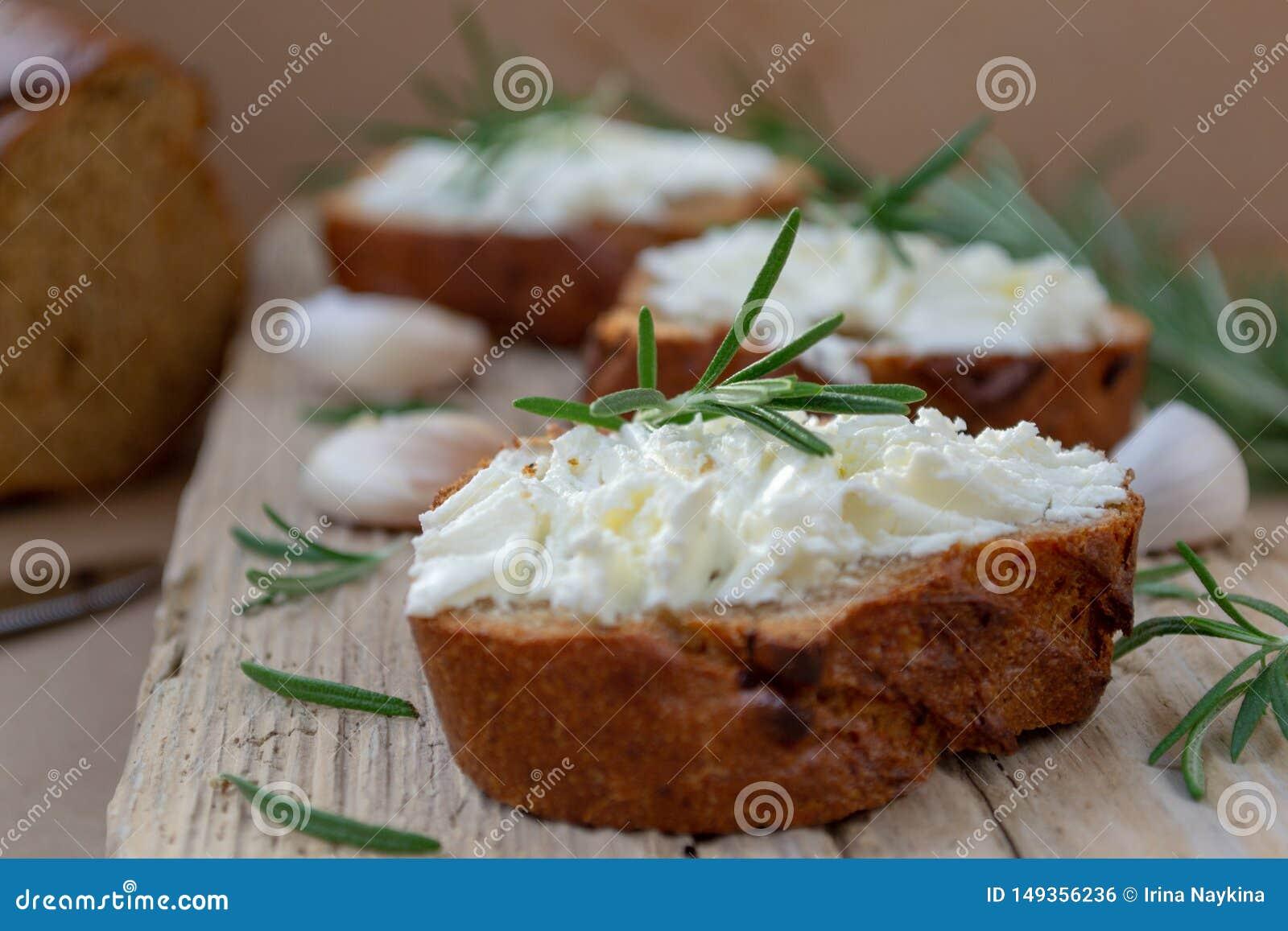 Τεμαχισμένο ψωμί με το ελαφρύ τυρί σε έναν ξύλινο πίνακα