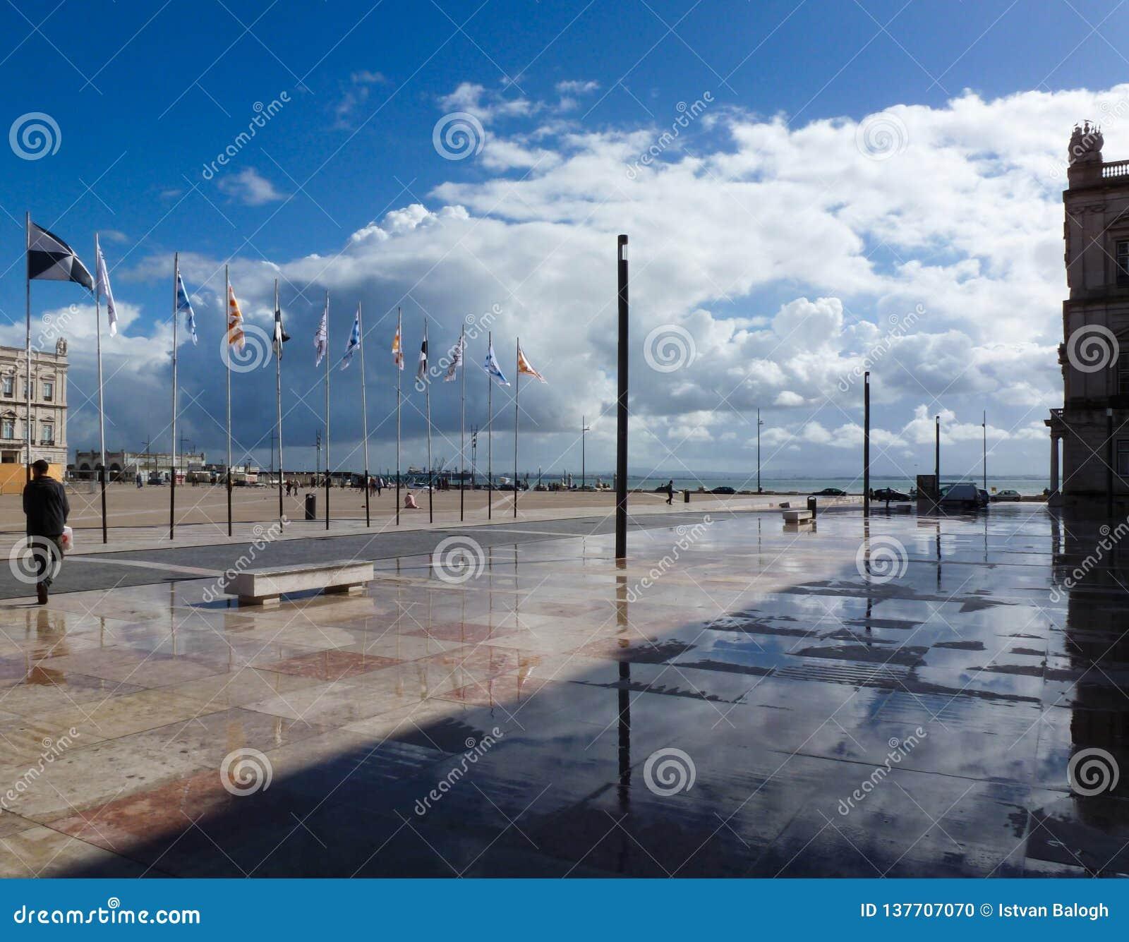 Τετράγωνο εμπορίου της Λισσαβώνας με το μπλε ουρανό, τα άσπρα σύννεφα και τις αντανακλάσεις