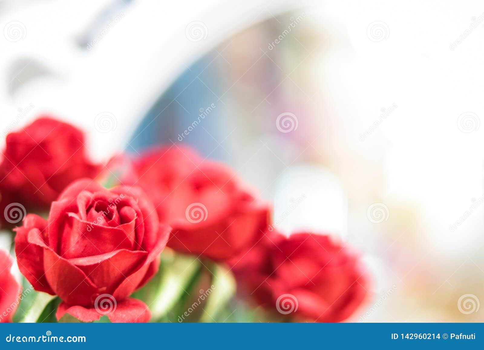 Τεχνητά κόκκινα τριαντάφυλλα στο θολωμένο υπόβαθρο