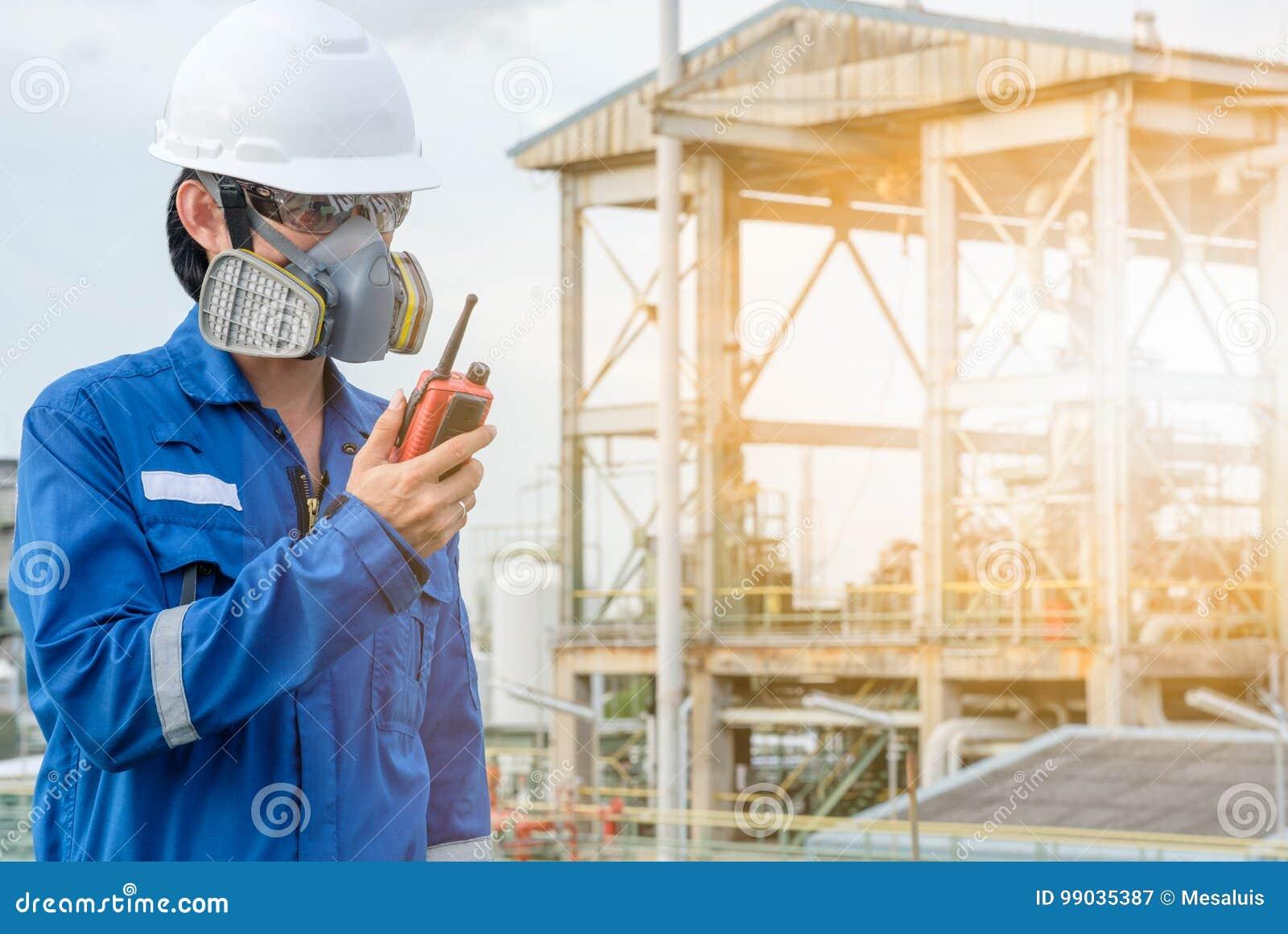 Τεχνικός με τη μάσκα αερίου ενάντια στο εργοστάσιο πετροχημικών