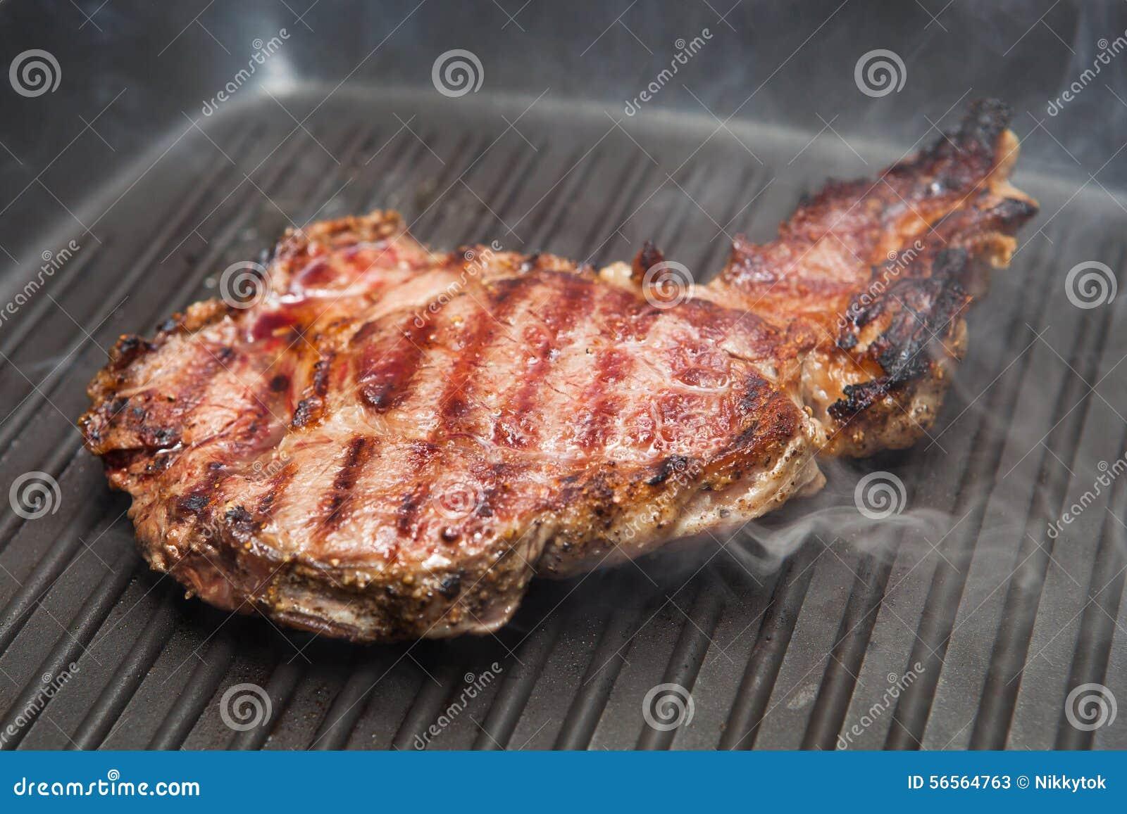Download Τηγανίζοντας μπριζόλα βόειου κρέατος σε ένα τηγάνι σχαρών Στοκ Εικόνα - εικόνα από εύγευστος, αδελφών: 56564763