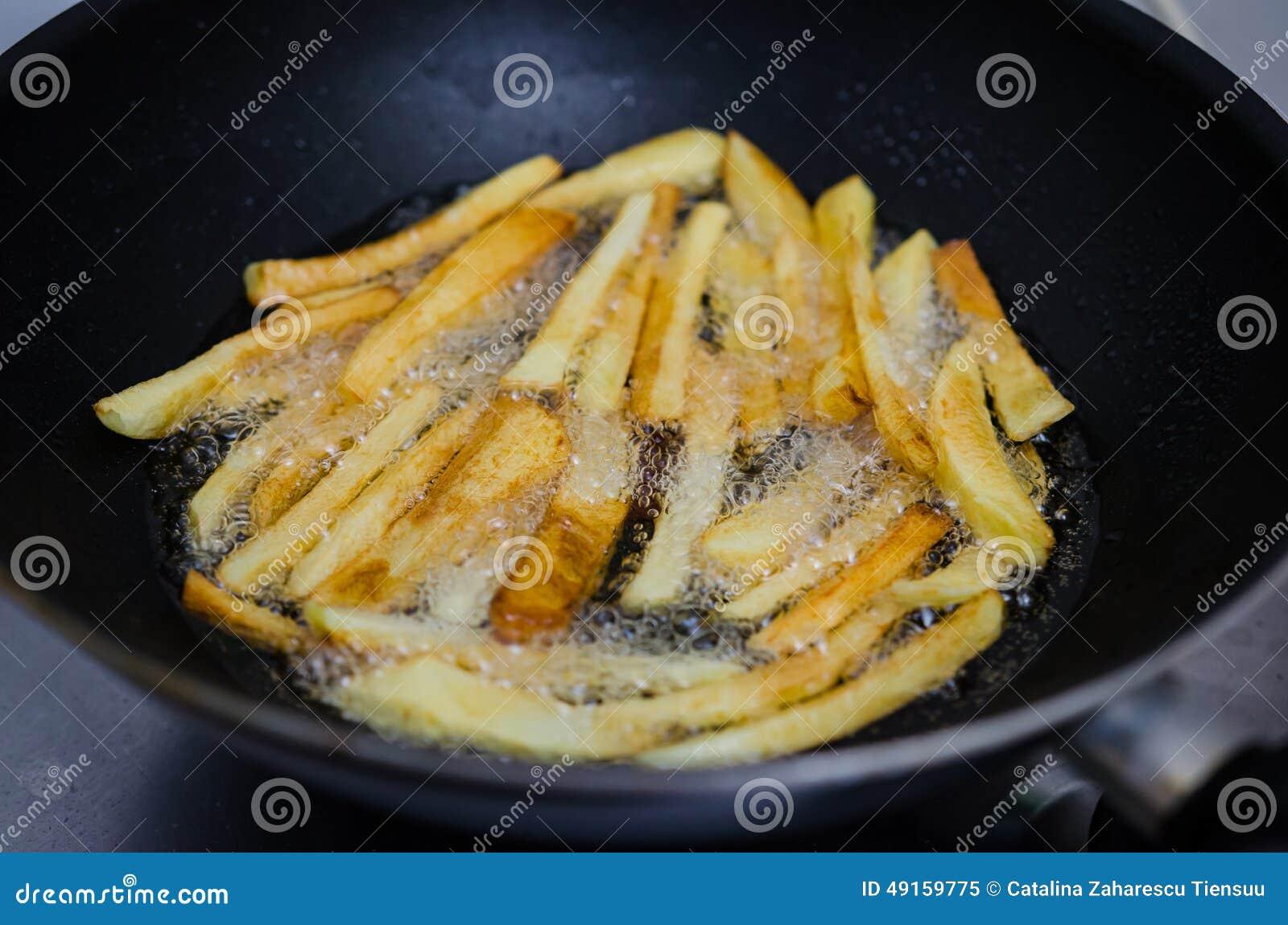 Τηγανίζοντας πατάτες σε ένα τηγάνι