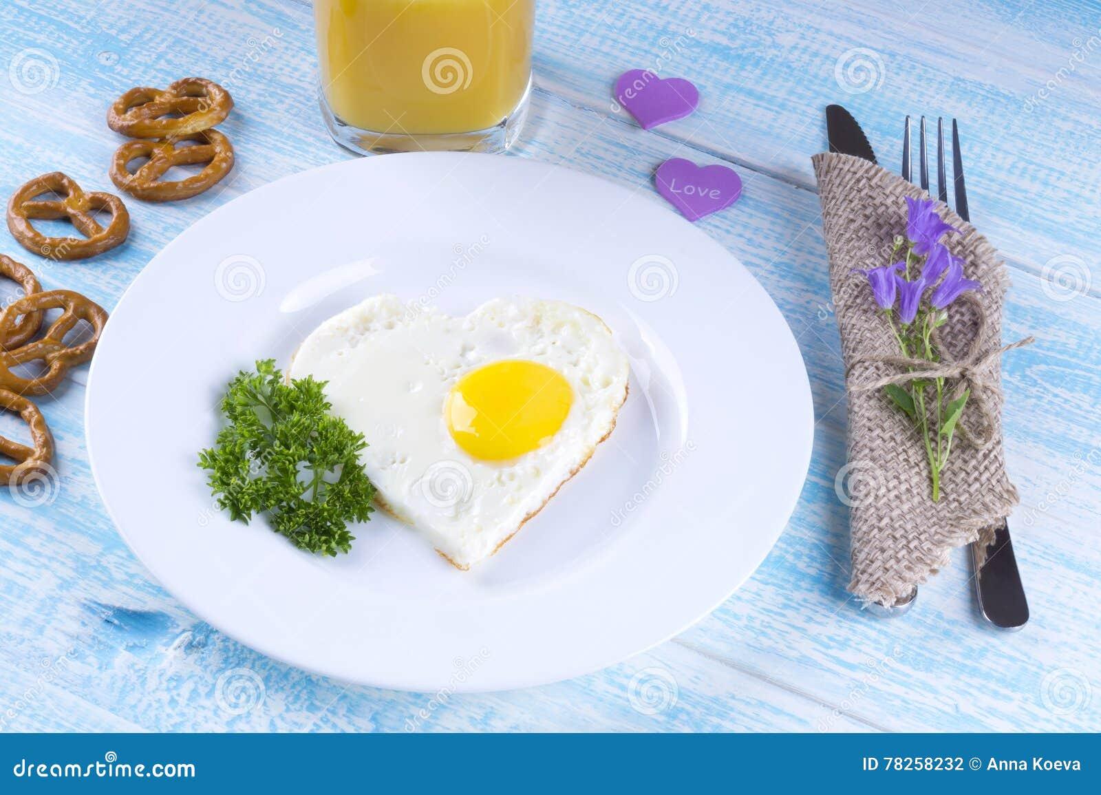 Τηγανισμένο αυγό με μορφή μιας καρδιάς, μια ανθοδέσμη των λουλουδιών, πρόσφατα