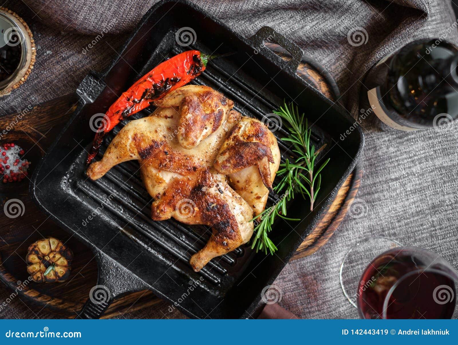 Τηγανισμένο κοτόπουλο ψητού σε ένα τηγανίζοντας τηγάνι σε έναν ξύλινο πίνακα