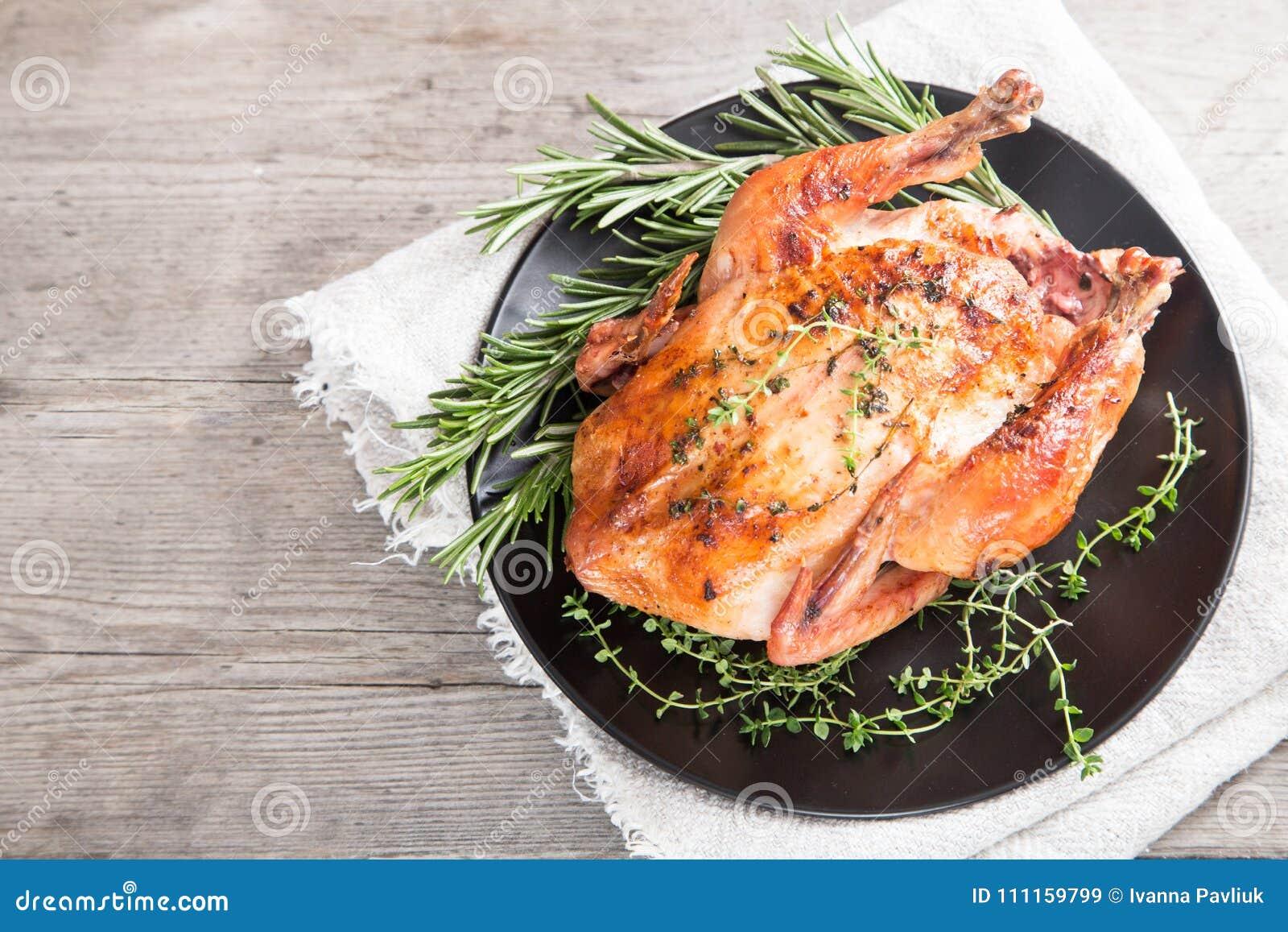 Τηγανισμένο ολόκληρο κοτόπουλο με τα χορτάρια πέρα από το φυσικό ξύλινο υπόβαθρο ποιοι