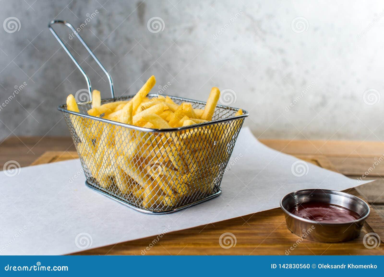 Τηγανιτές πατάτες στο πλέγμα και τη σάλτσα σιδήρου