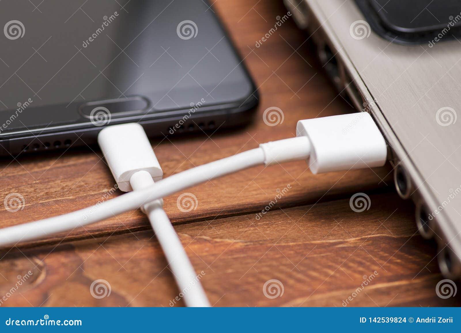 Τηλέφωνο που συνδέεται κινητό με το lap-top Ένα καλώδιο USB συνδέει το τηλέφωνο και το lap-top στον ξύλινο πίνακα Έξυπνο τηλέφωνο