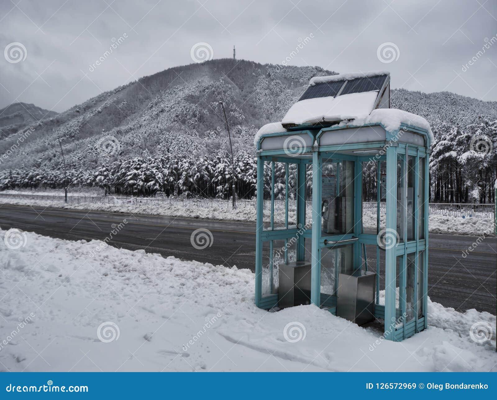 Τηλεφωνικός θάλαμος σε έναν χιονισμένο δρόμο βουνών