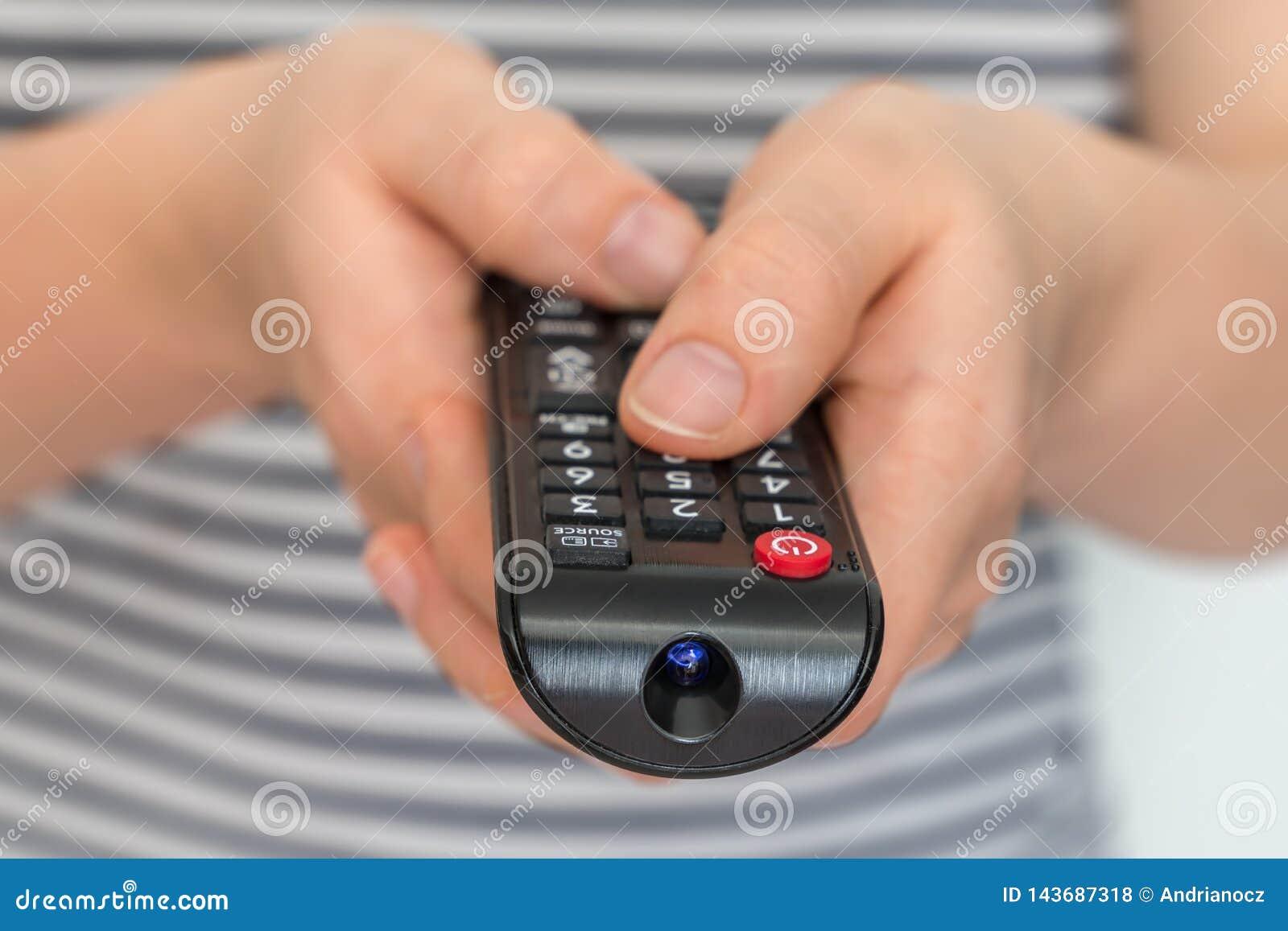 Τηλεχειρισμός στα θηλυκά χέρια που δείχνει τη TV