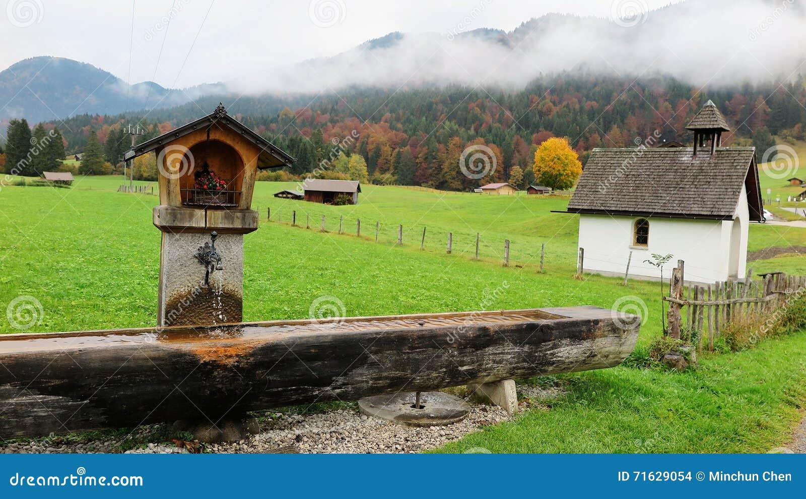 Τοπίο ενός βαυαρικού καλλιεργήσιμου εδάφους με μια ξύλινη γούρνα, τα εξοχικά σπίτια & τις σιταποθήκες σε ένα αγρόκτημα σε ένα ομι