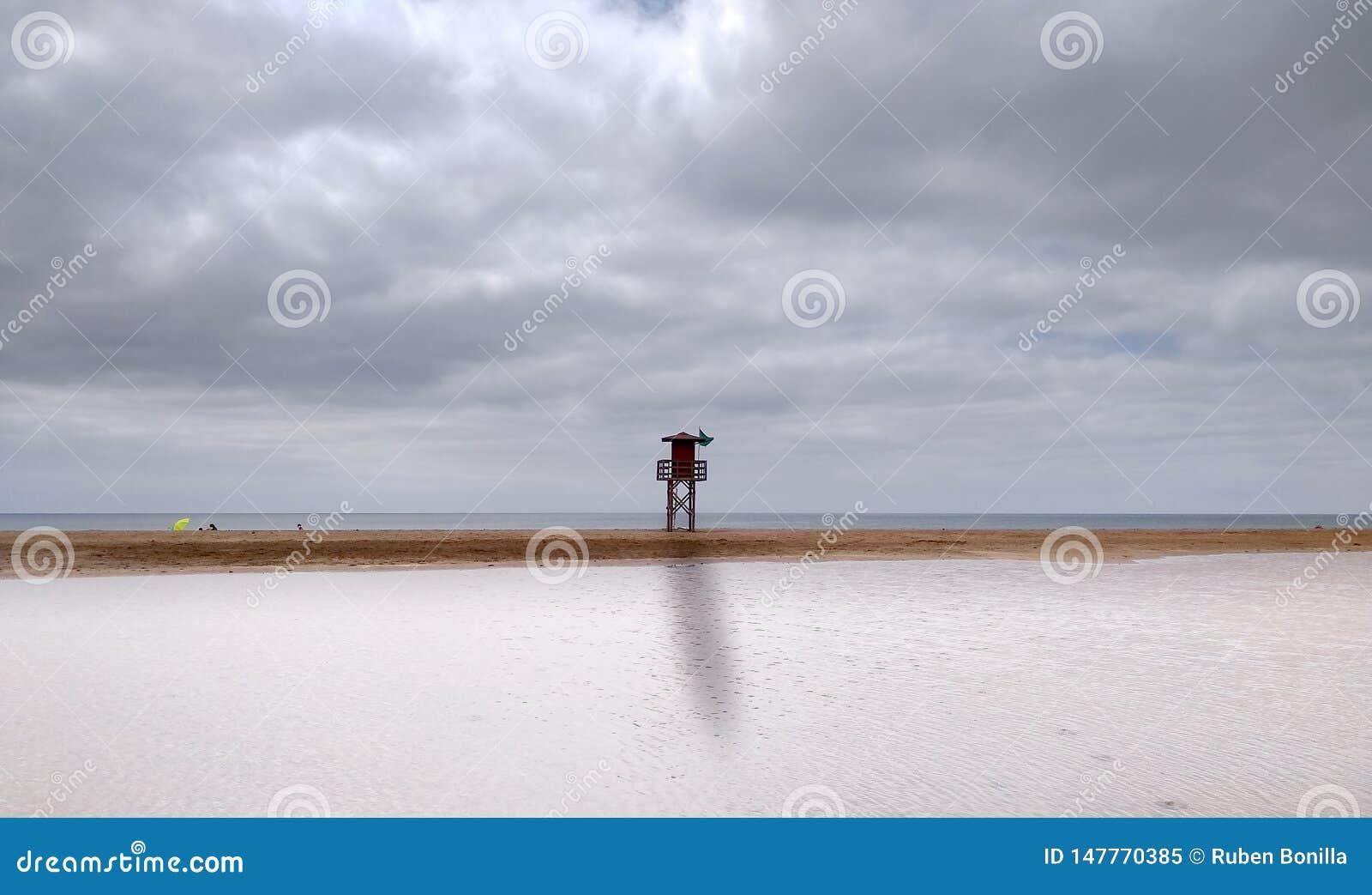 τοπίο μιας παραλίας με το νεφελώδη ουρανό και ενός ψηλού σταθμού lifeguard με την πράσινη σημαία στη μέση Καταρχάς το θαλάσσιο νε
