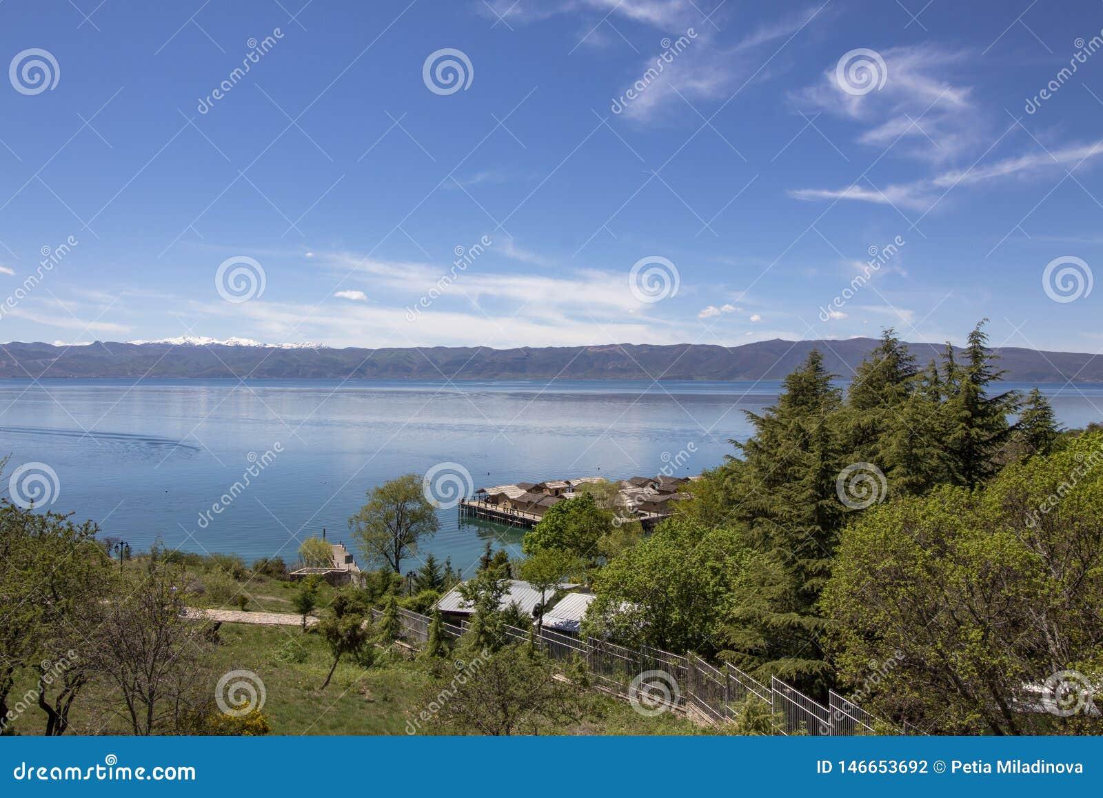Τοπίο πέρα από το Κόλπο των κόκκαλων με τα σπίτια σωρών Λίμνη της Οχρίδας