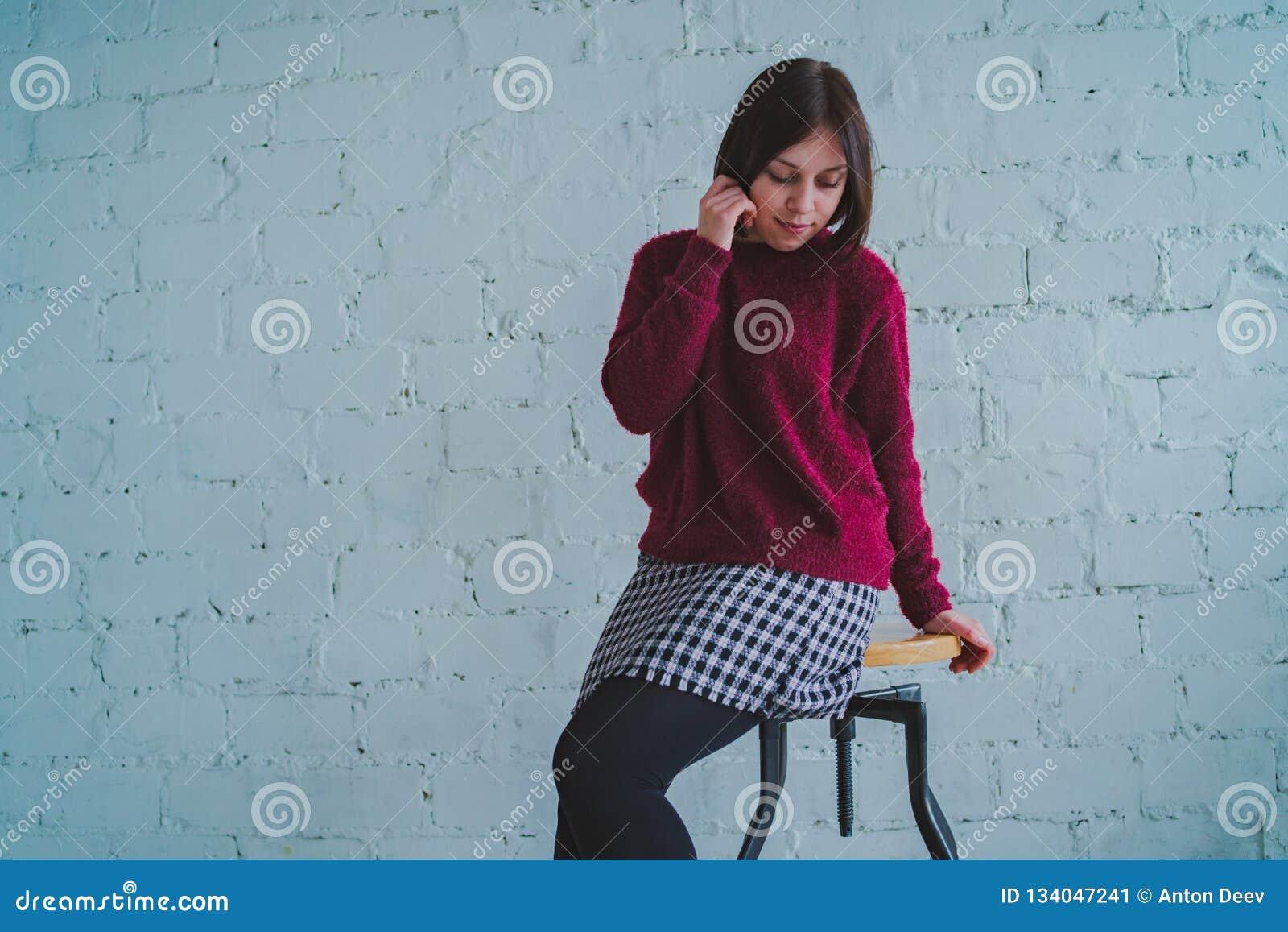 Τοποθέτηση Brunette με μια καρέκλα, ενάντια σε έναν τουβλότοιχο