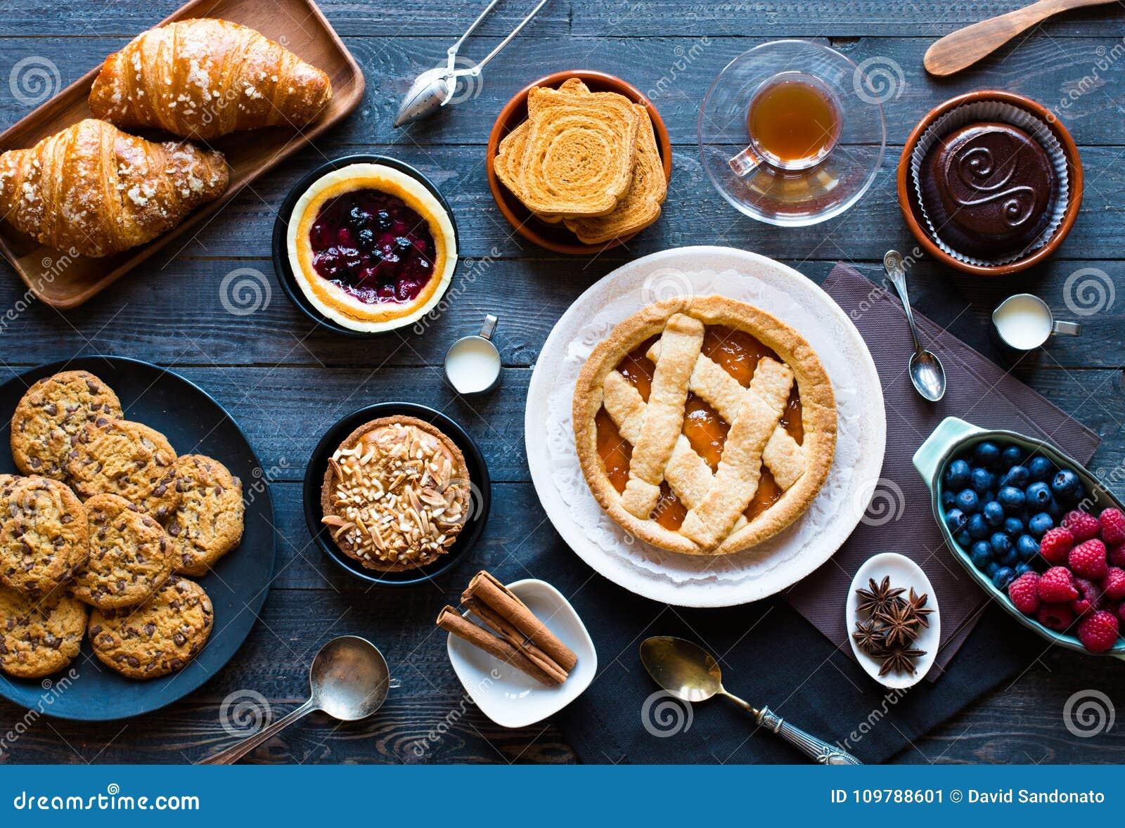 Τοπ άποψη ενός ξύλινου επιτραπέζιου συνόλου των κέικ, φρούτα, καφές, μπισκότα