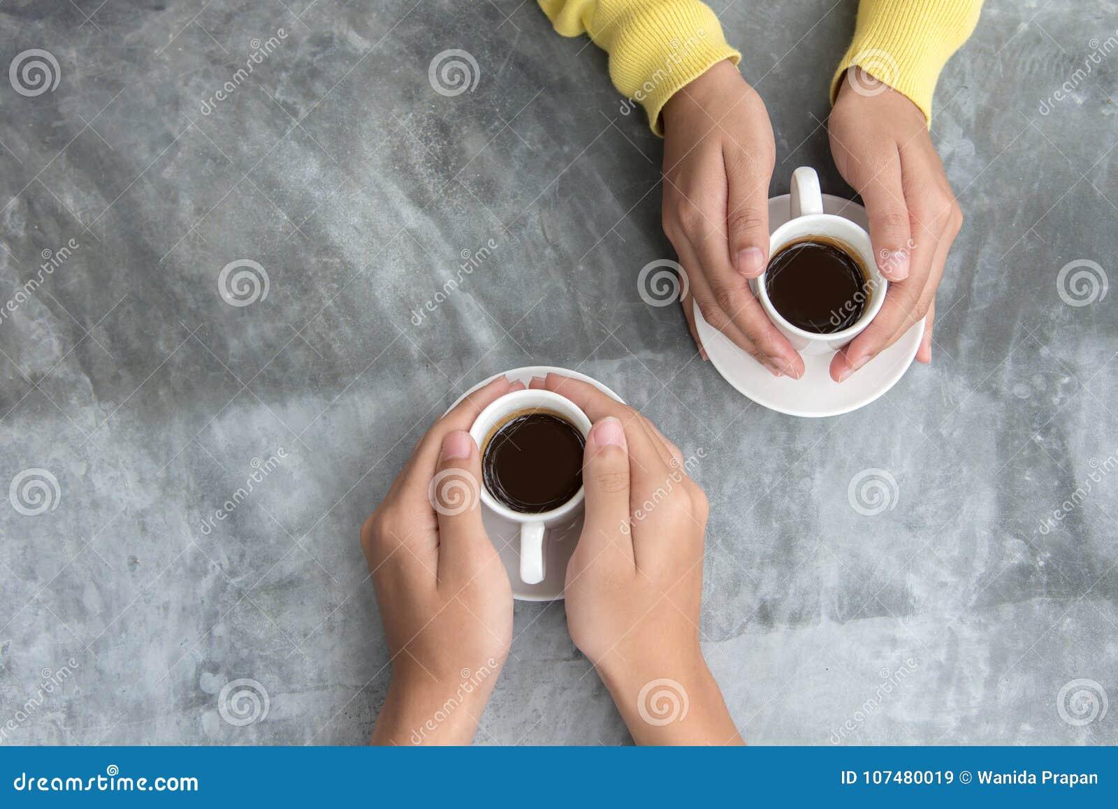 Τοπ άποψη με το διάστημα αντιγράφων Ερωτευμένα χέρια εκμετάλλευσης ζεύγους με την αγάπη καφέ στον πίνακα