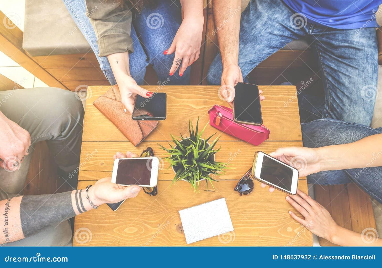 Τοπ άποψη μιας ομάδας φίλων hipster που κάθονται σε έναν καφέ φραγμών που χρησιμοποιεί το κινητό έξυπνο τηλέφωνο - νέα νέα τάση π