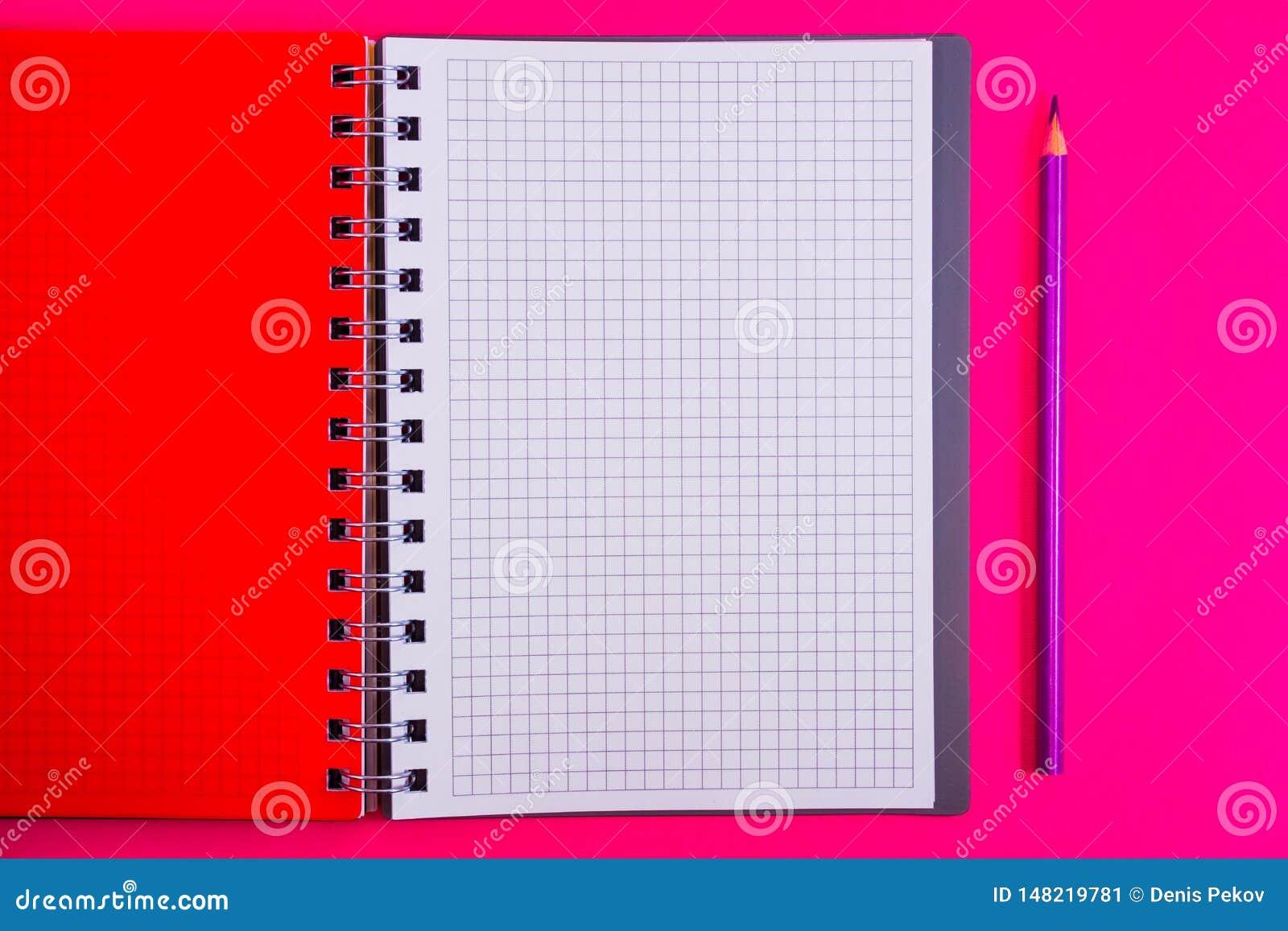 Τοπ άποψη του ανοικτού σπειροειδούς κενού σημειωματάριου με το μολύβι στο κόκκινο υπόβαθρο γραφείων
