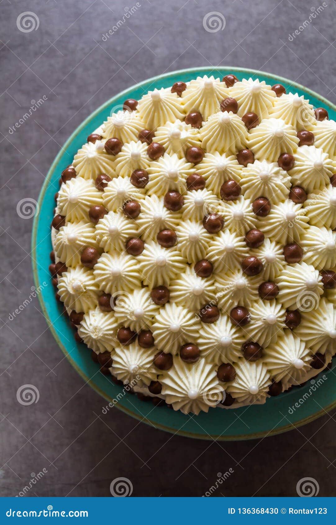 Τοπ άποψη του διακοσμημένου κέικ γενεθλίων με την κτυπημένη καραμέλα κρέμας και σοκολάτας στο τυρκουάζ πιάτο στο σκοτεινό γκρίζο