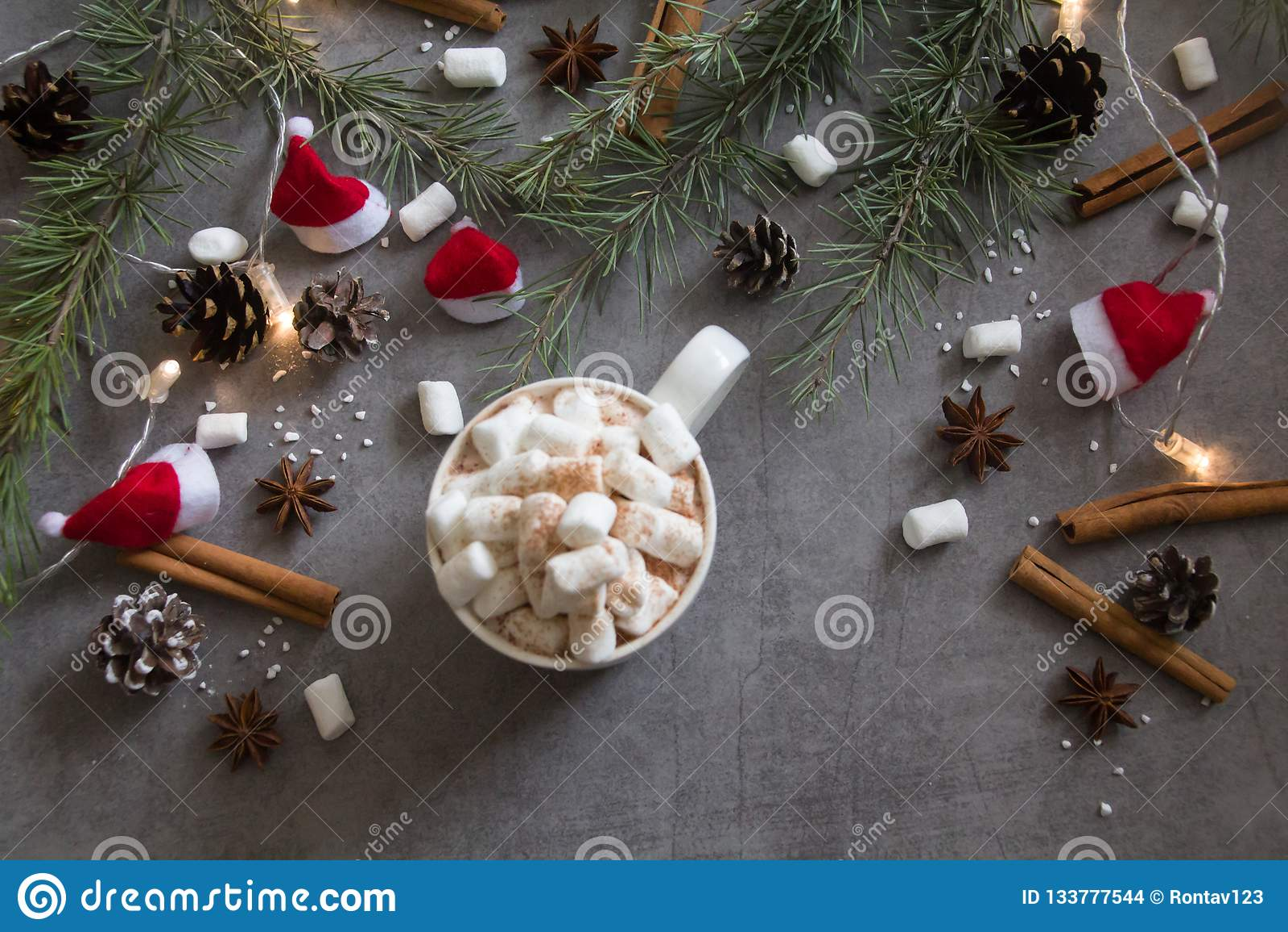 Τοπ άποψη του καυτά φλυτζανιού και marshmallows σοκολάτας στο γκρίζο κλίμα με το θέμα Χριστουγέννων