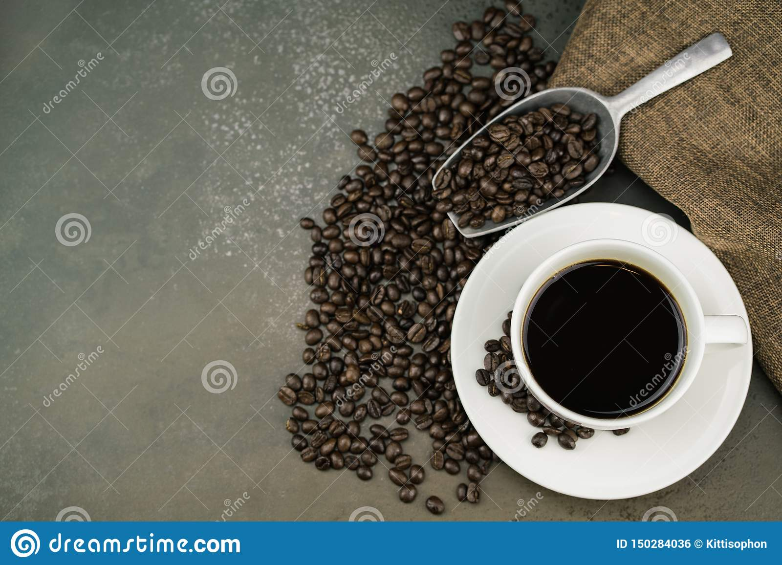 Τοπ άποψη του καυτού καφέ στο άσπρο φλυτζάνι με τα φασόλια καφέ ψητού, την τσάντα και τη σέσουλα στο επιτραπέζιο υπόβαθρο πετρών
