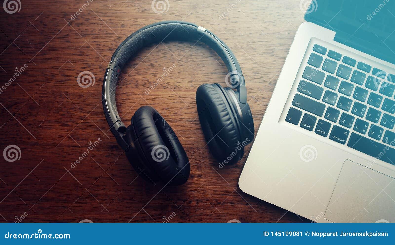 Τοπ άποψη του μαύρου ακουστικού bluetooth με το φορητό προσωπικό υπολογιστ
