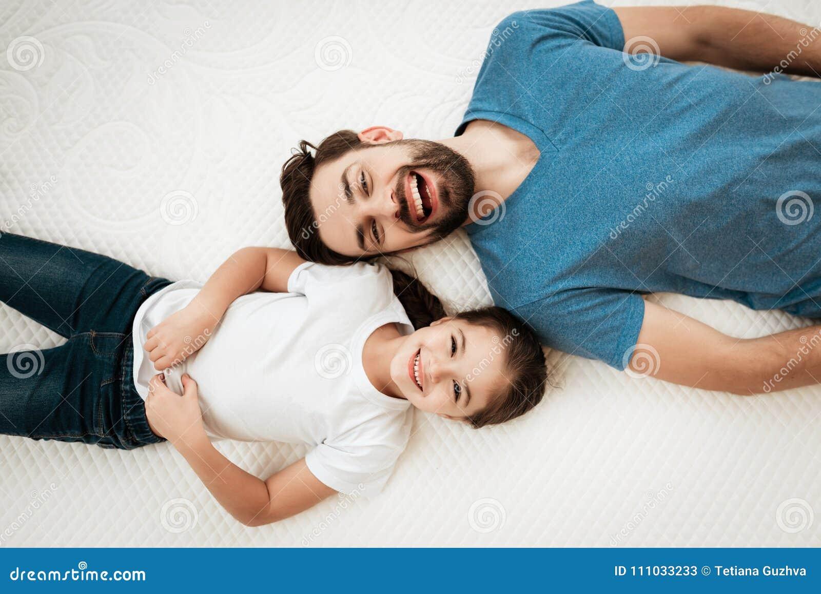 Τοπ άποψη του πατέρα και της κόρης Το ενήλικο ευτυχές γενειοφόρο άτομο με χαριτωμένο λίγη κόρη βρίσκεται στο κρεβάτι στο κατάστημ