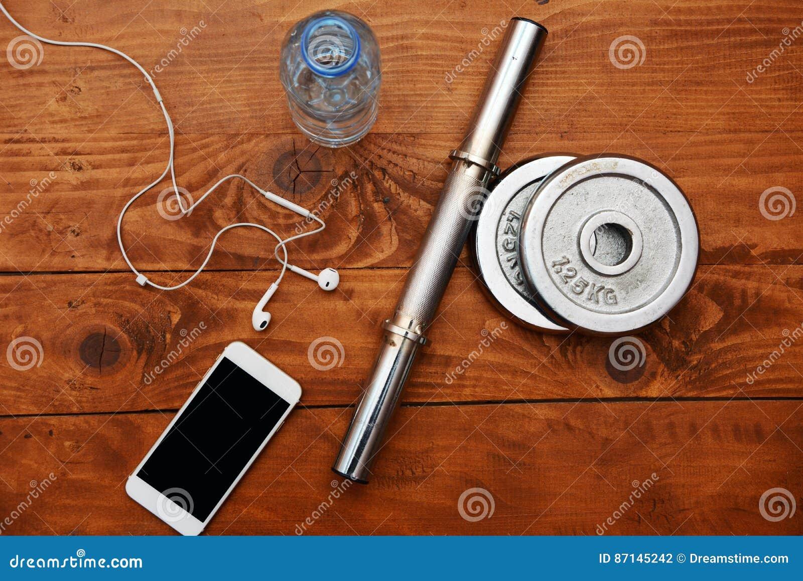 Τοπ άποψη του smartphone, των ακουστικών, του μπουκαλιού νερό και των βαρών στο ξύλινο υπόβαθρο Κλείστε επάνω την όψη