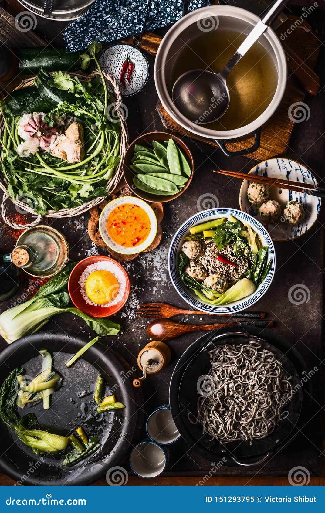 Τοπ άποψη των ασιατικών πιάτων τροφίμων Ασιατική προετοιμασία σούπας νουντλς στο σκοτεινό αγροτικό πίνακα κουζινών Δοχείο με το α
