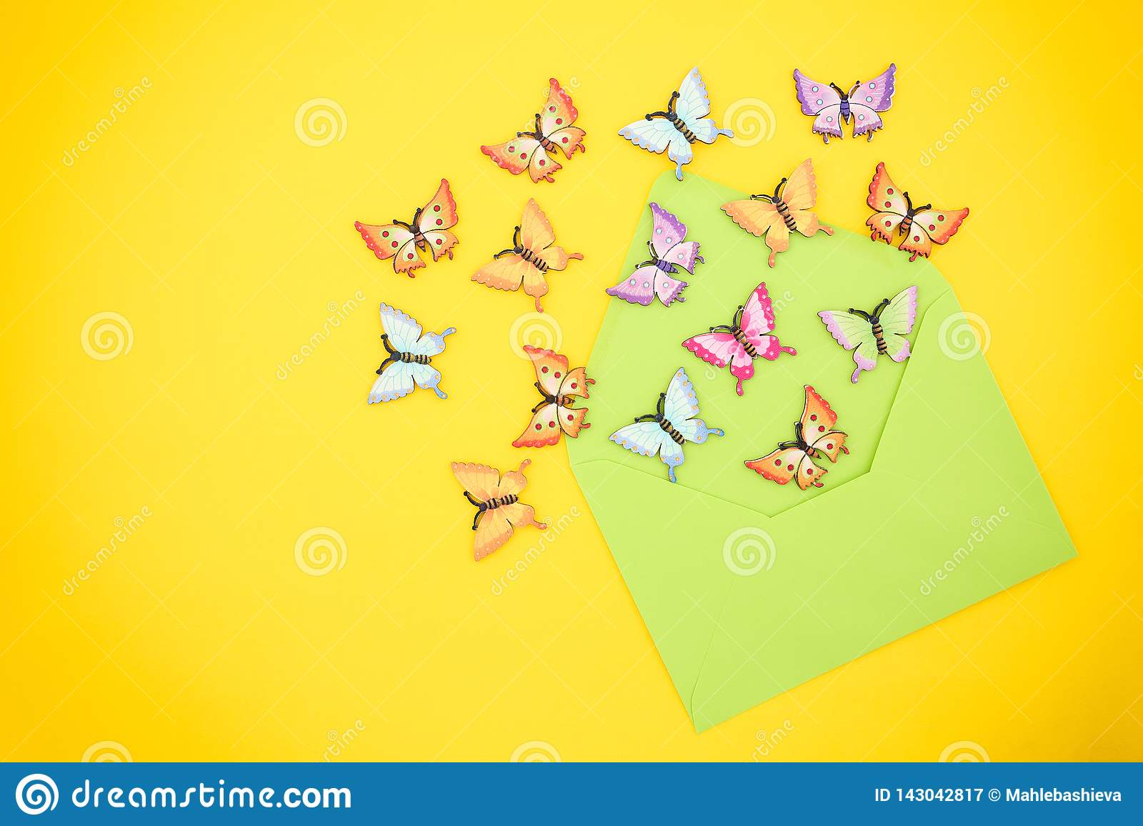 Τοπ άποψη των διακοσμητικών, πολύχρωμων πεταλούδων που βγαίνουν από έναν ανοικτό, πράσινο φάκελο από το ανακυκλωμένο έγγραφο για