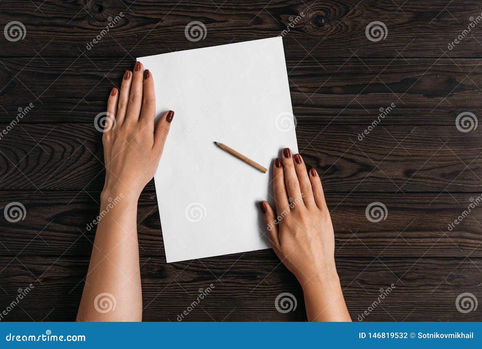 Τοπ άποψη των χεριών των γυναικών, έτοιμη να γράψει κάτι σε ένα κενό κομμάτι χαρτί που βρίσκεται σε έναν ξύλινο πίνακα Άσπρο κενό