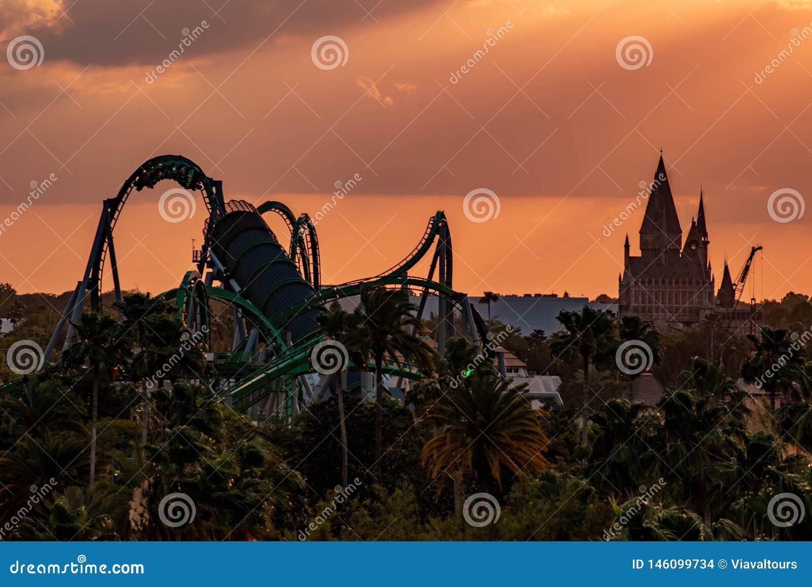 Τοπ άποψη Hogwarts Castle και απίστευτο Hulk rollercoaster στο ζωηρόχρωμο υπόβαθρο ουρανού ηλιοβασιλέματος στην περιοχή UNIVERSAL