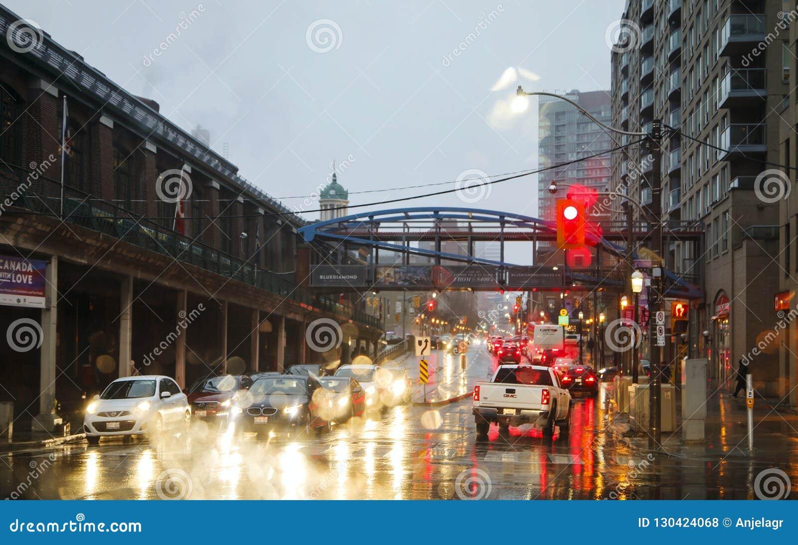 ΤΟΡΟΝΤΟ, ΚΑΝΑΔΑΣ - 18 ΝΟΕΜΒΡΊΟΥ 2017: Οδός στη βροχή στο βράδυ στο φως από τα φω τα φωτεινού σηματοδότη και αυτοκινήτων στο Τορόν