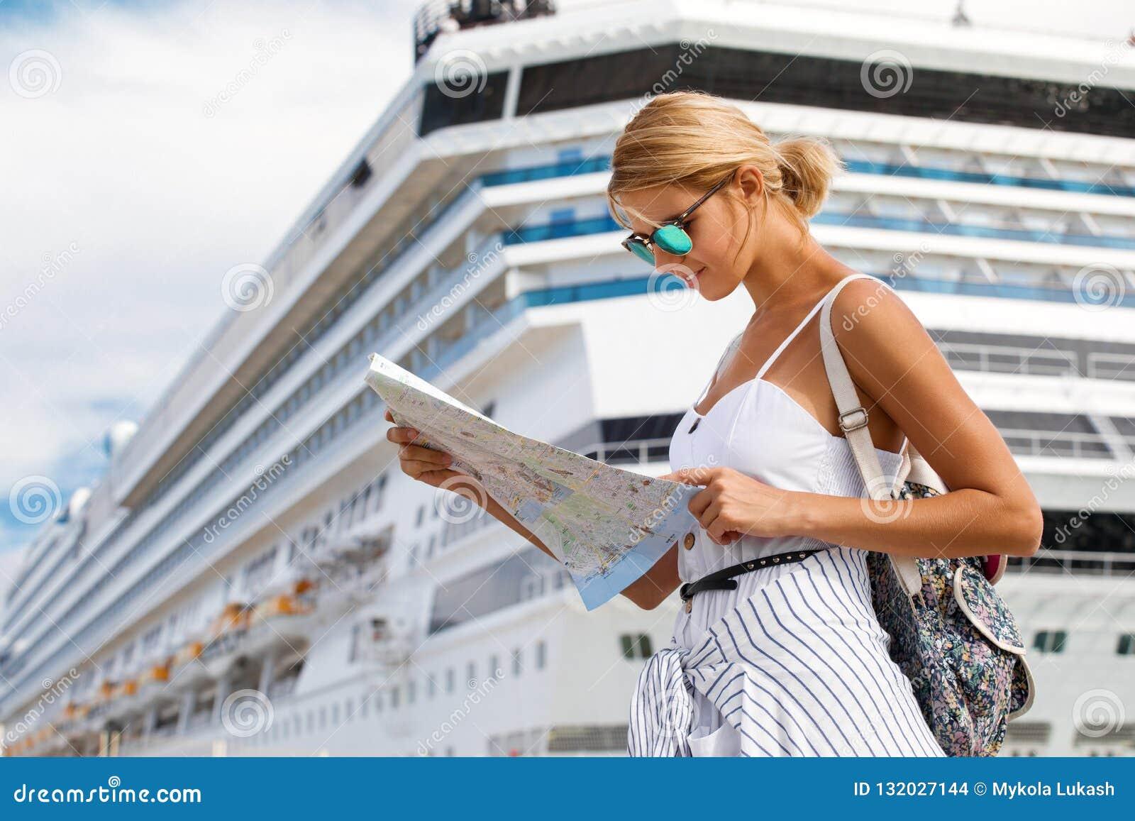 Τουρίστας γυναικών με το χάρτη, που στέκεται μπροστά από το μεγάλο σκάφος της γραμμής κρουαζιέρας, θηλυκό ταξιδιού