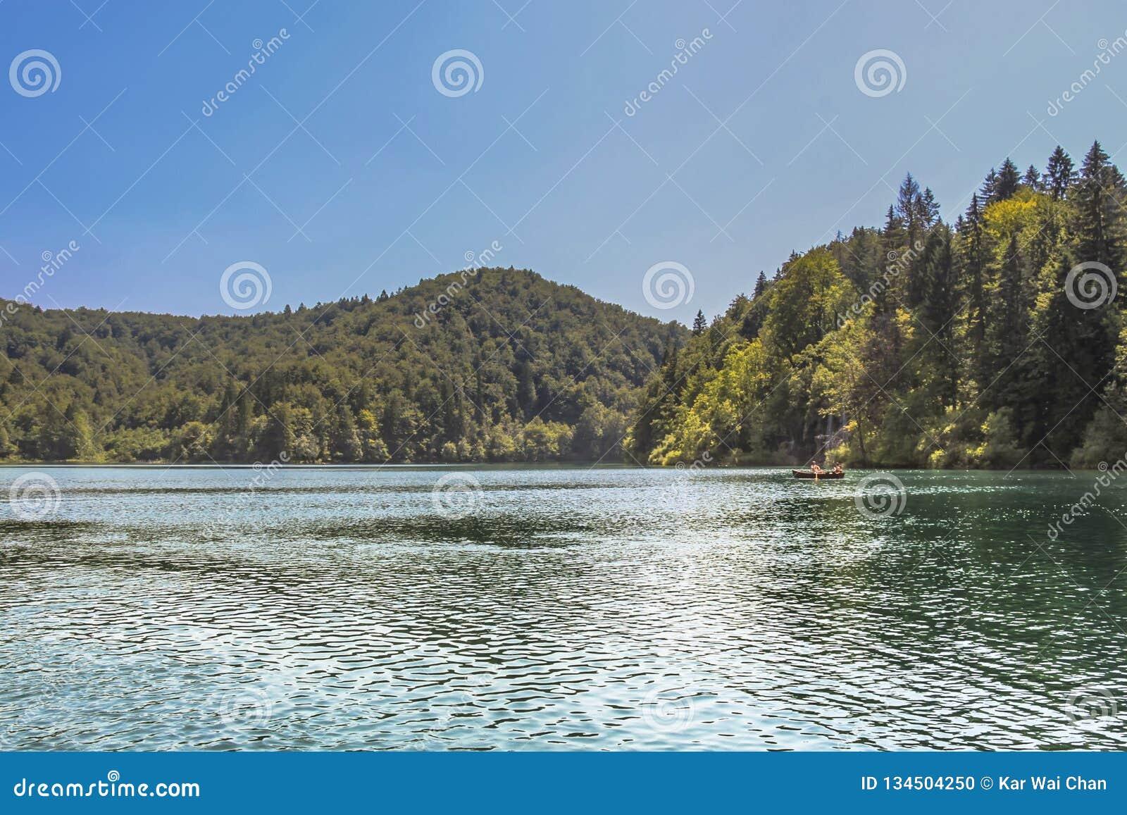 Τουρίστας που παίρνει έναν γύρο βαρκών στις λίμνες στο εθνικό πάρκο λιμνών Plitvice