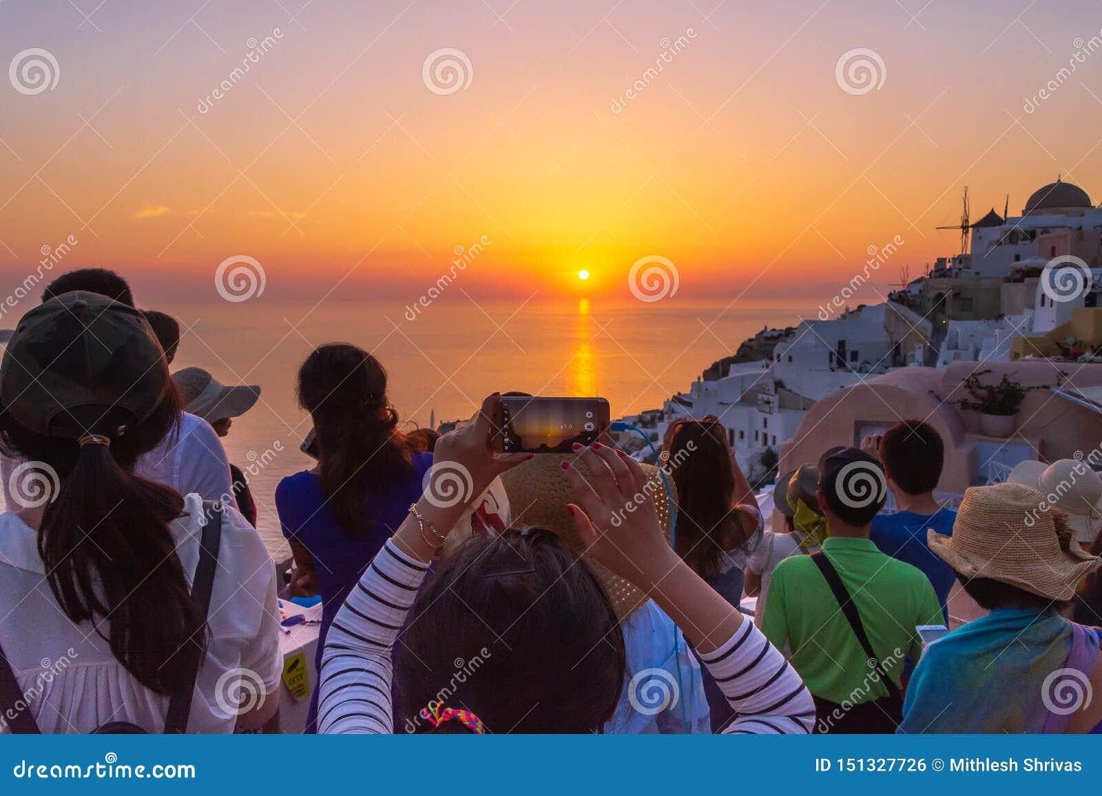 Τουρίστας που παίρνει την εικόνα του όμορφου ηλιοβασιλέματος σε Santorini, Ελλάδα