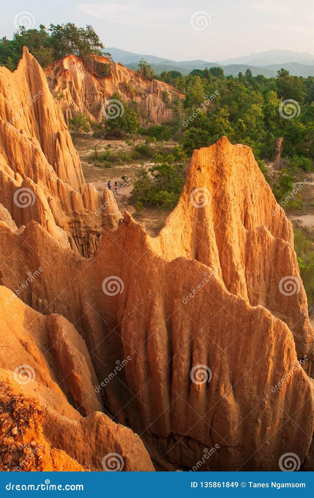 Τουρίστες ζεύγους στο αρχαίο φυσικό τοπίο στο ηλιοβασίλεμα Η περιοχή NA Noi Σάο DIN επιδεικνύει το γραφικό τοπίο του διαβρωμένου