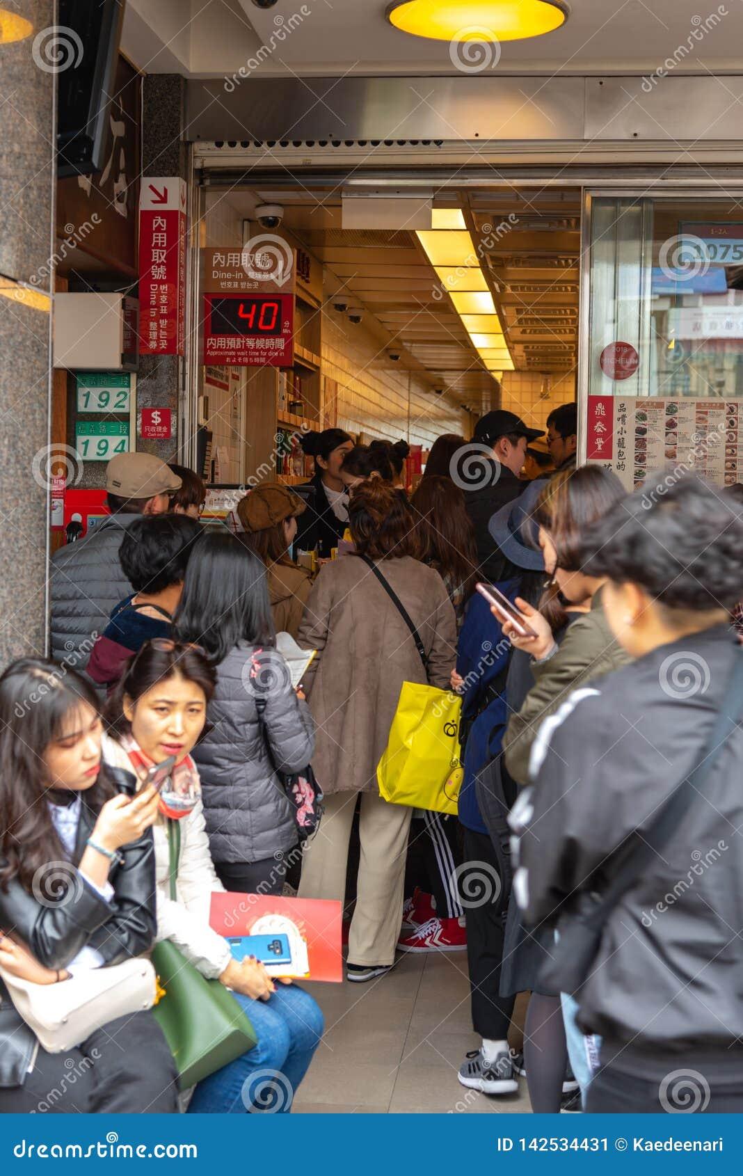 Τουρίστες που περιμένουν στη σειρά στο αρχικό εστιατόριο DIN Tai Fung mainstore στο δρόμο Xinyi Το Michelin απονεμημένο αστέρι Di