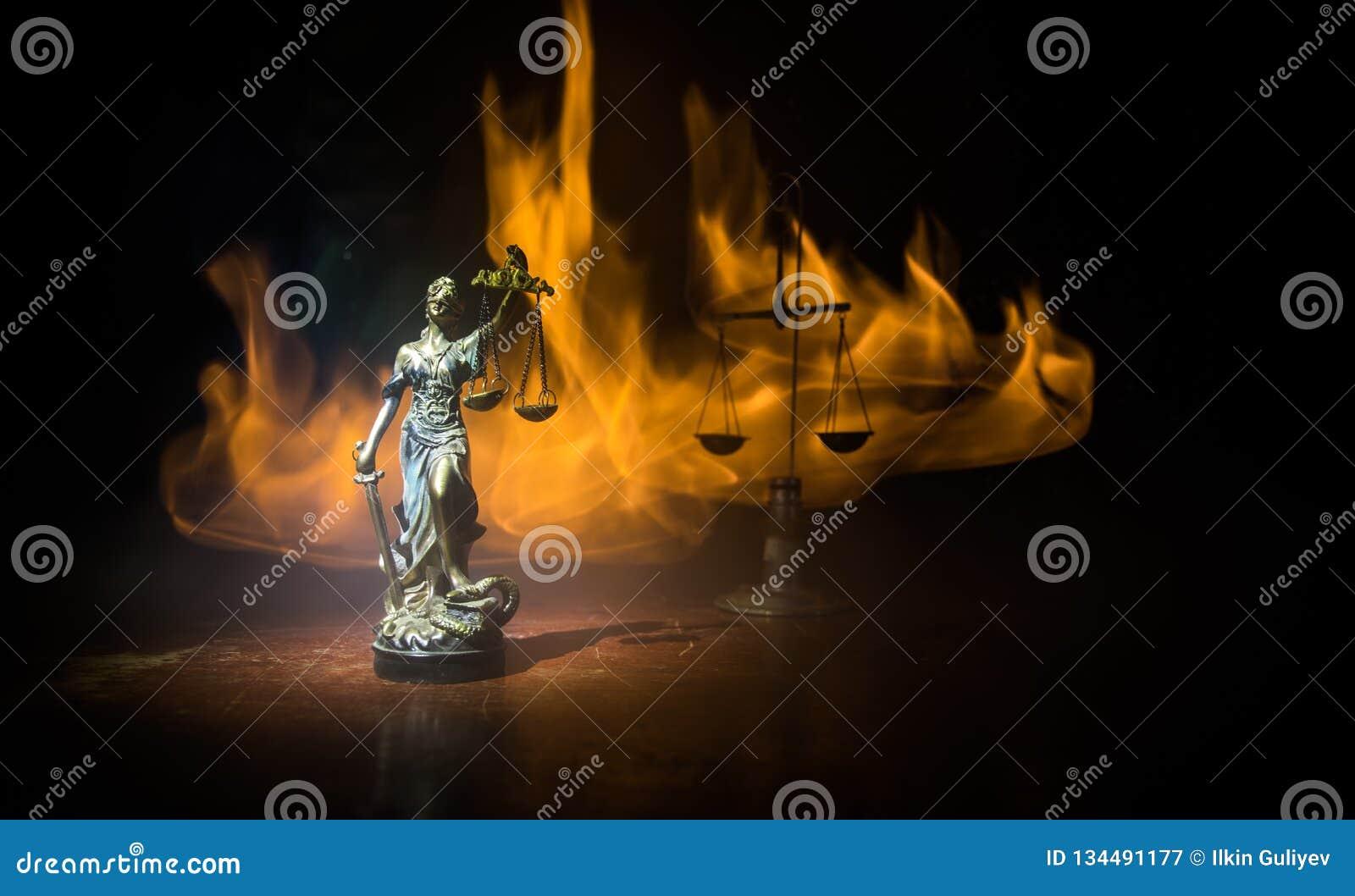 Το άγαλμα της δικαιοσύνης - γυναικείο δικαιοσύνη ή Iustitia/Justitia η ρωμαϊκή θεά της δικαιοσύνης σε ένα σκοτεινό υπόβαθρο πυρκα
