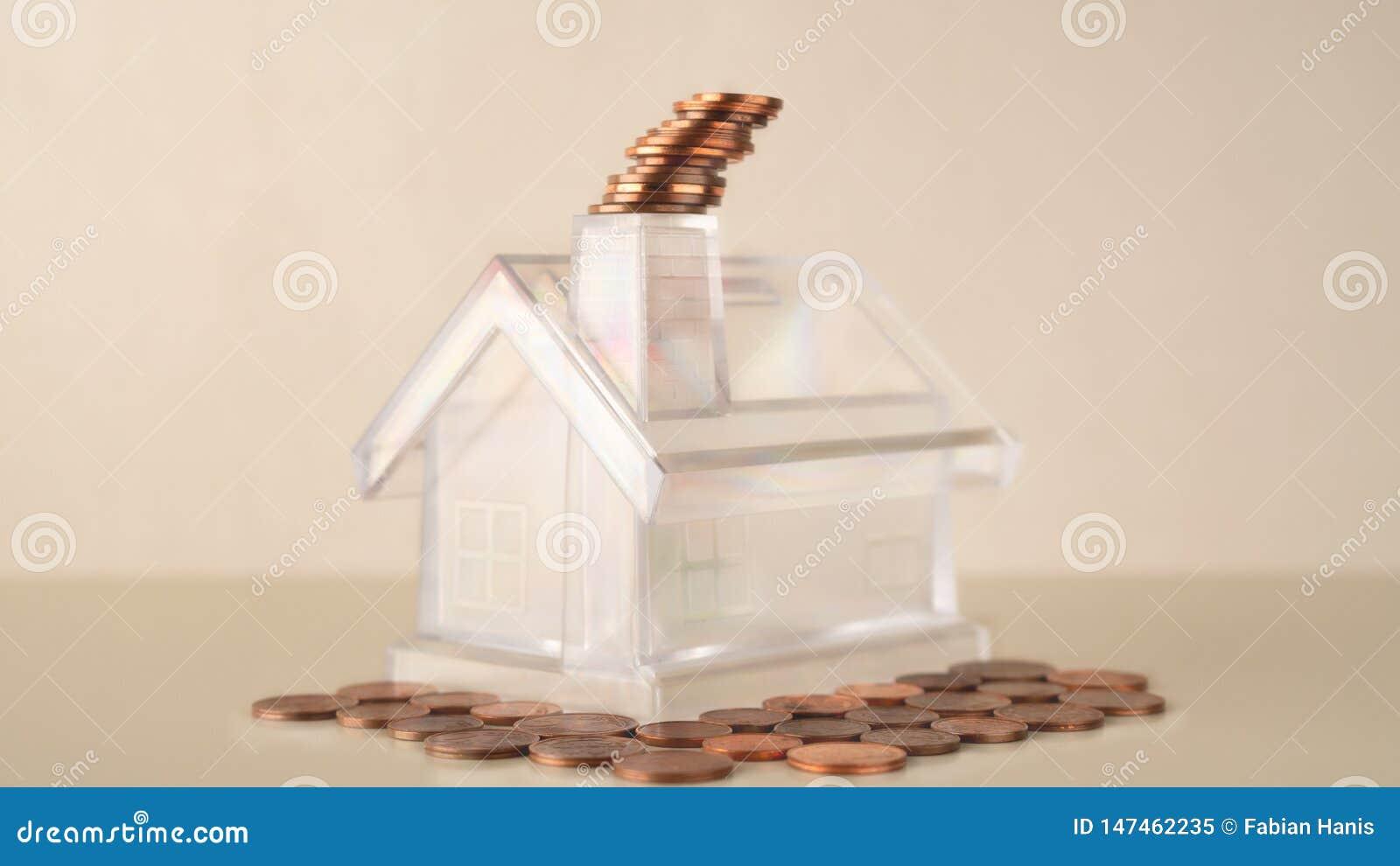 Το άσπρο διαφανές σπίτι τραπεζών Piggy με την καπνοδόχο, νομίσματα συσσωρεύει τον καπνό, τη διοικητική επιχείρηση οικονομικούς κα