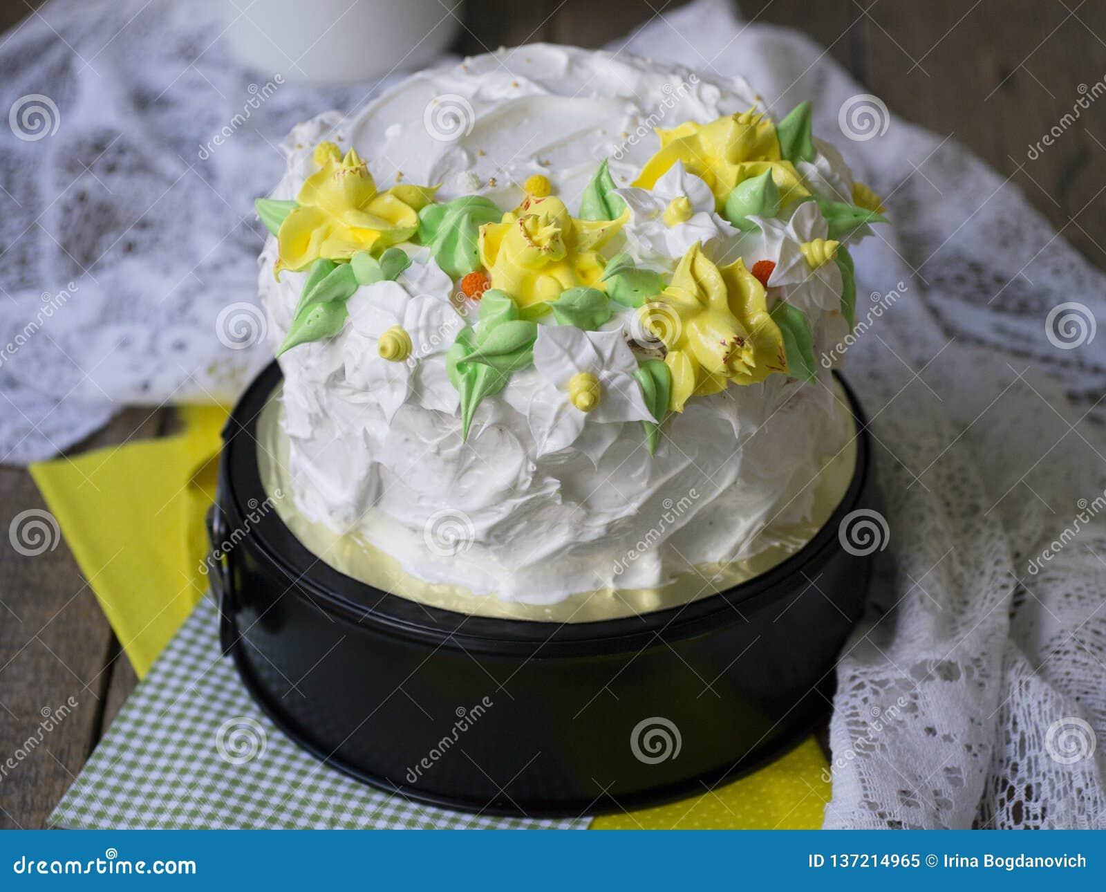 Το άσπρο κέικ που διακοσμείται με την άνοιξη κρέμας ανθίζει - daffodils - στο ξύλινο υπόβαθρο με το ύφασμα δαντελλών Τρύγος, αναδ