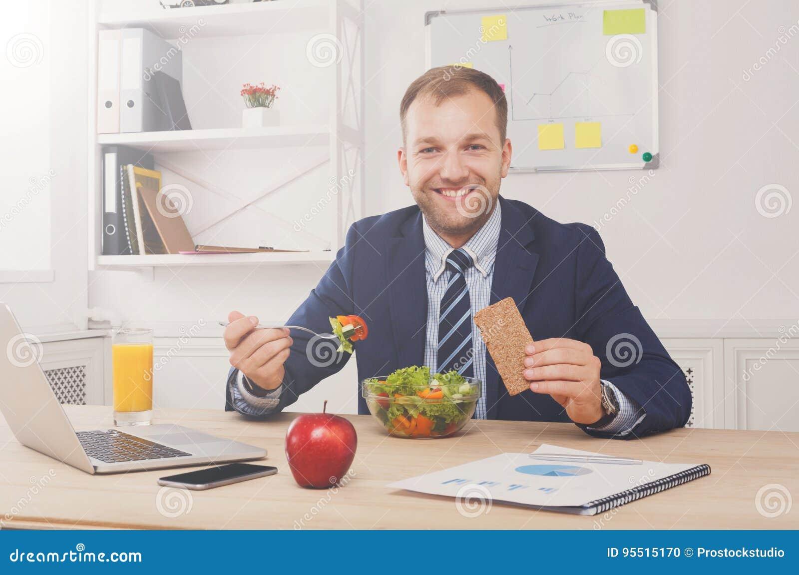 Το άτομο έχει το υγιές επιχειρησιακό μεσημεριανό γεύμα στο σύγχρονο εσωτερικό γραφείων